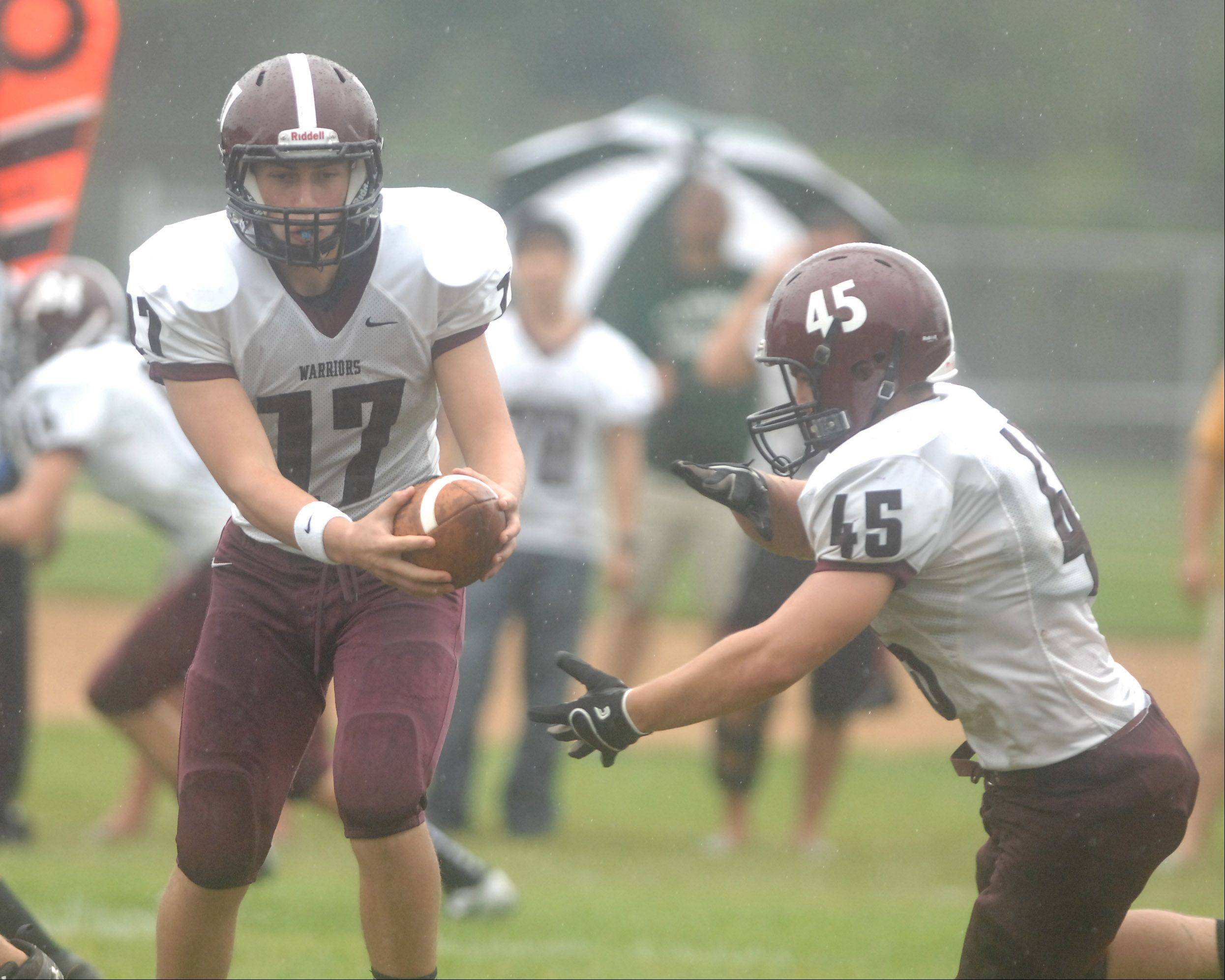 Nate Martinez hands the ball to John Gemmel, of of Wheaton Academy, during the Wheaton Academy vs. Immaculate Conception gme in Elmhurst Saturday.