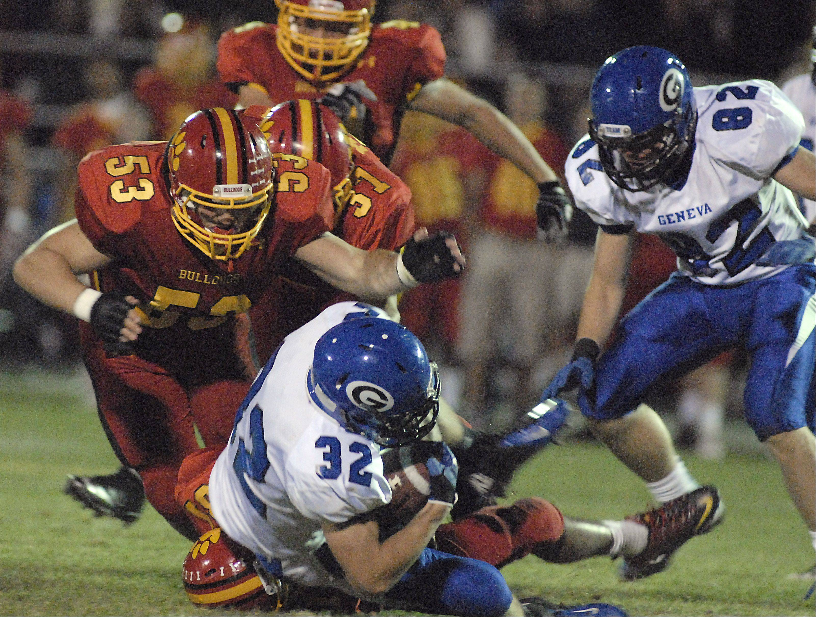Geneva's Travis Champer is taken down by Batavia's Vincent Cerezo and Michael Gates in the second quarter.