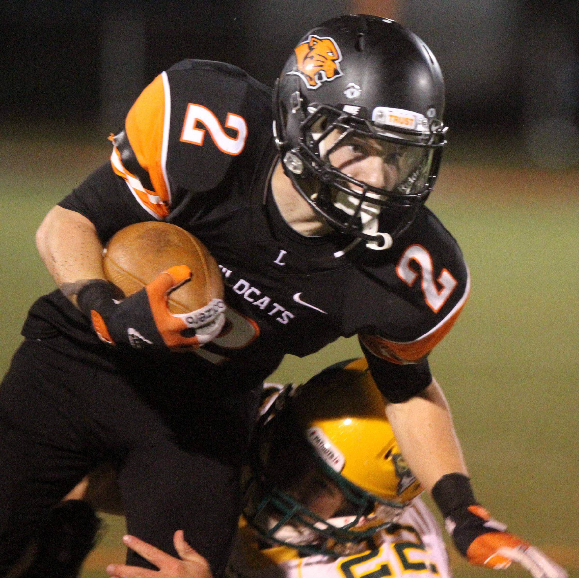 Libertyville running back Conor Simpson tucks the ball in against Stevenson defender Timmy Breen .