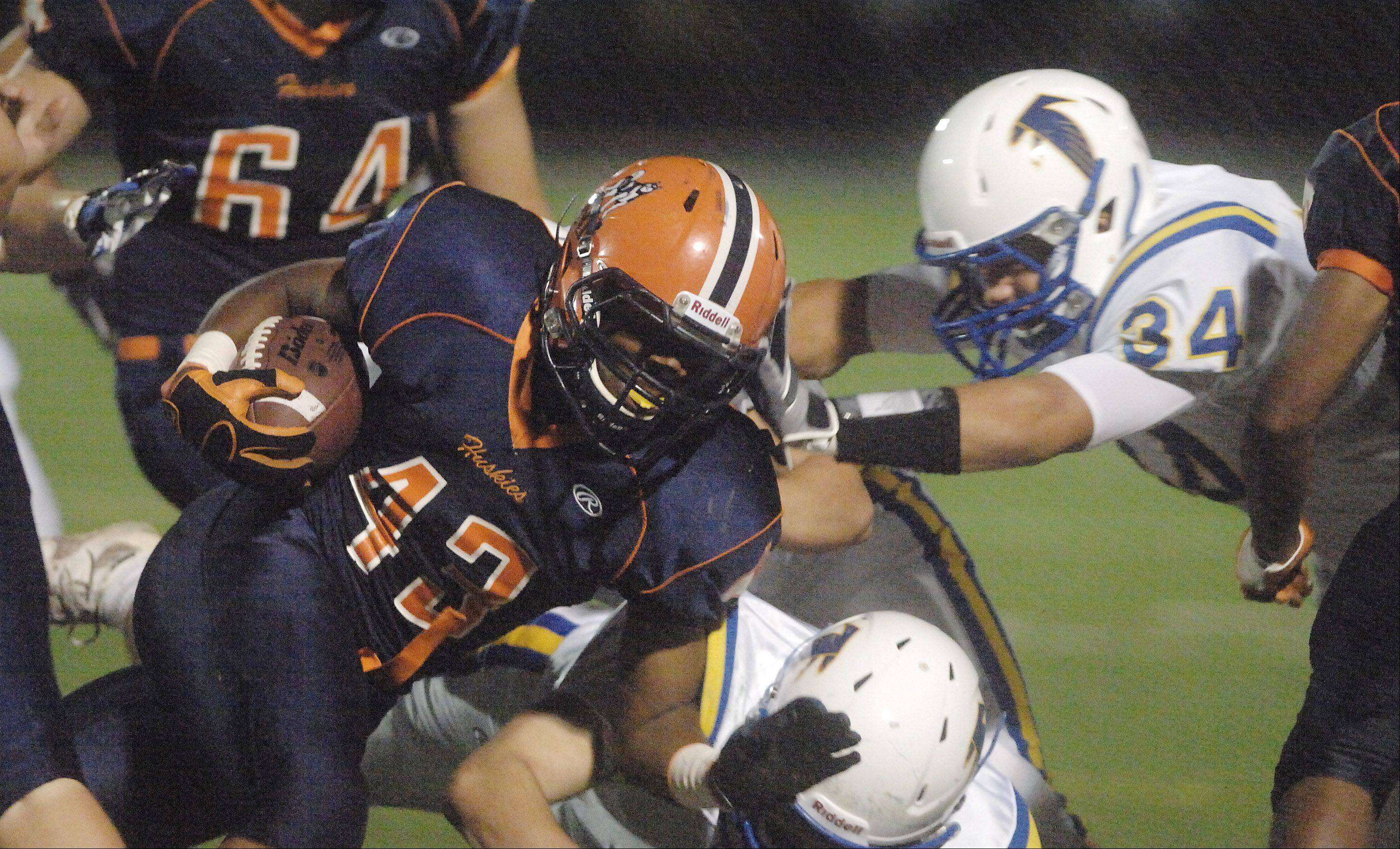 Desean Brown of Naperville North is pulled down by JD Marconi of Wheaton North.