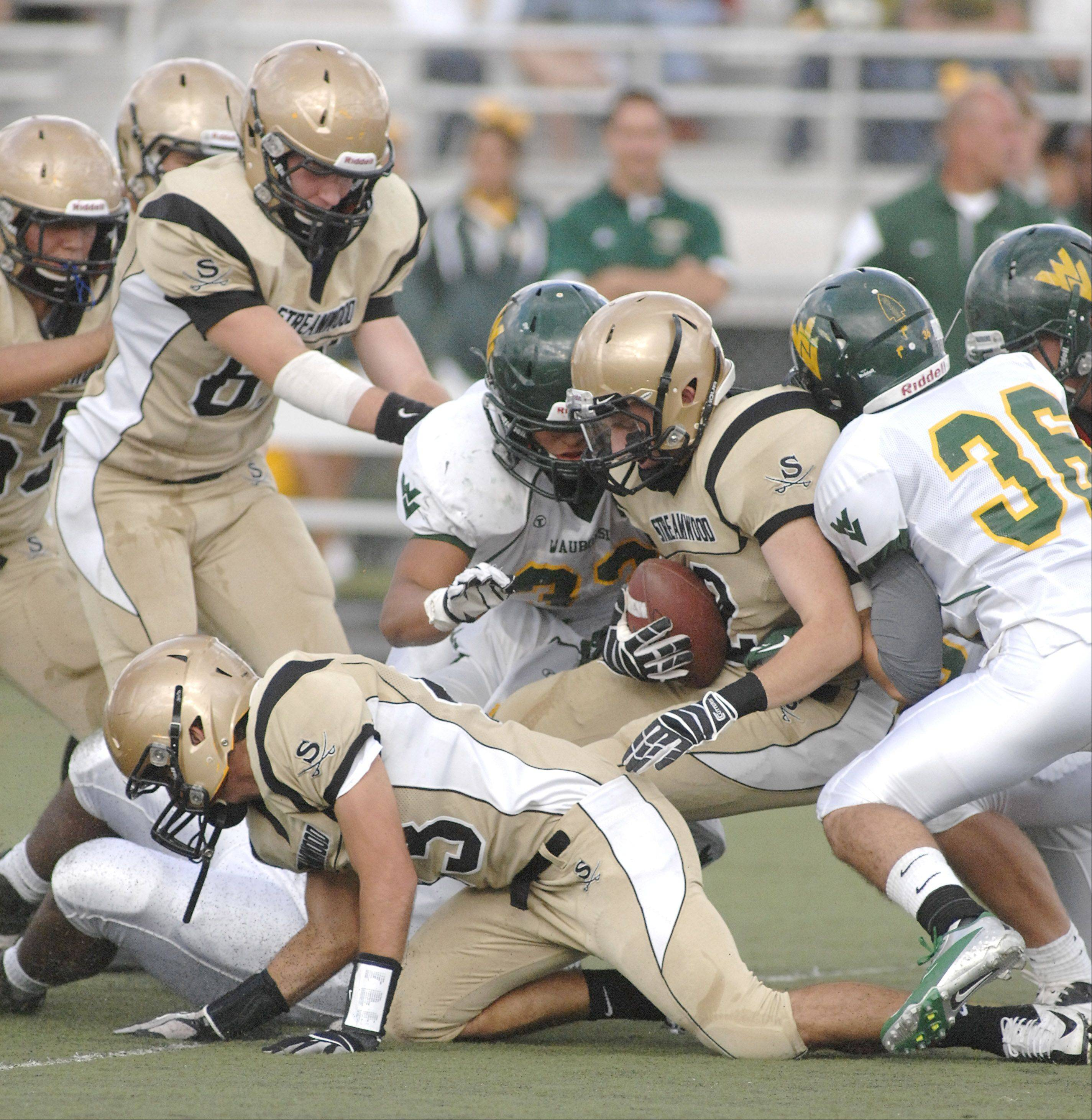 Streamwood's Tyler Hendershot is bought down in a mass tackle in the second quarter on Saturday, September 8.