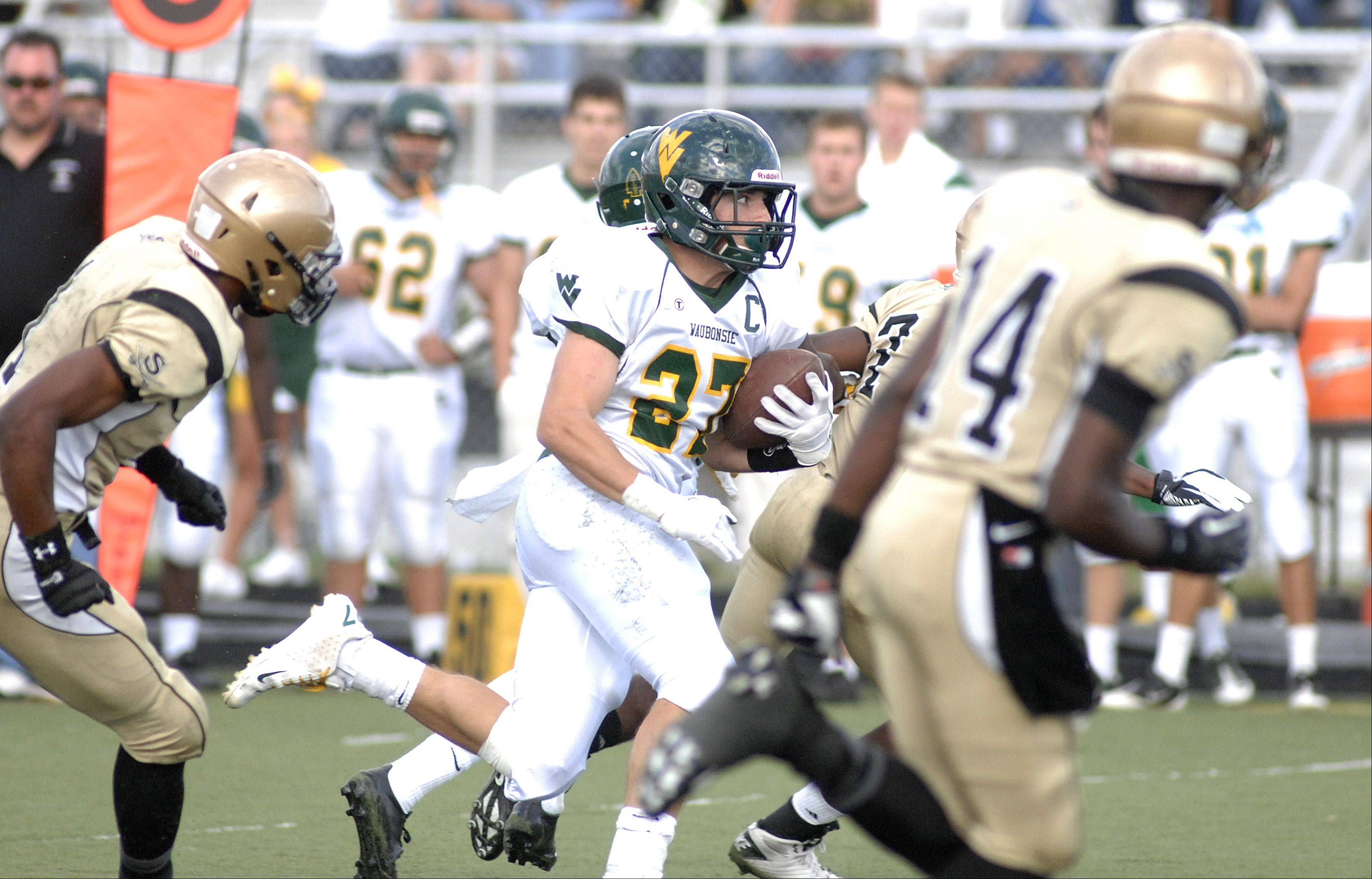 Waubonsie Valley's Austin Guido blazes through an attempted block by Streamwood to score a touchdown in the first quarter on Saturday, September 8.