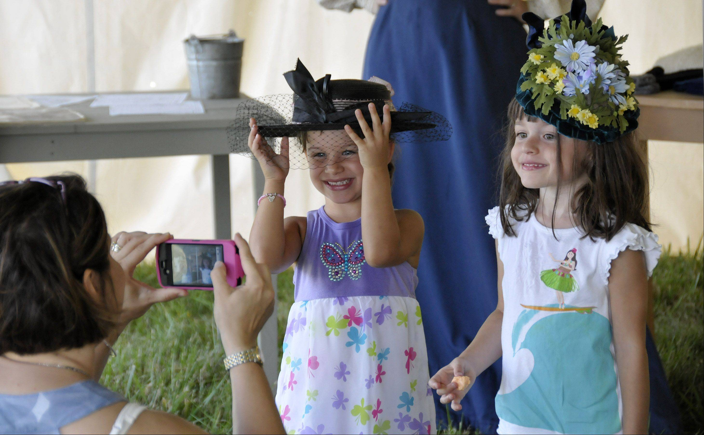 Eniko Camberis, center, and her sister Makena, right, get to try on old-fashioned hats while their mother Susan Camberis, left, takes their picture. The DuPage Forest Preserve district is holding an old-fashioned country fair Sunday at Kline Creek Farm in West Chicago, to give people the experience of what an 1890s fair would have been like.