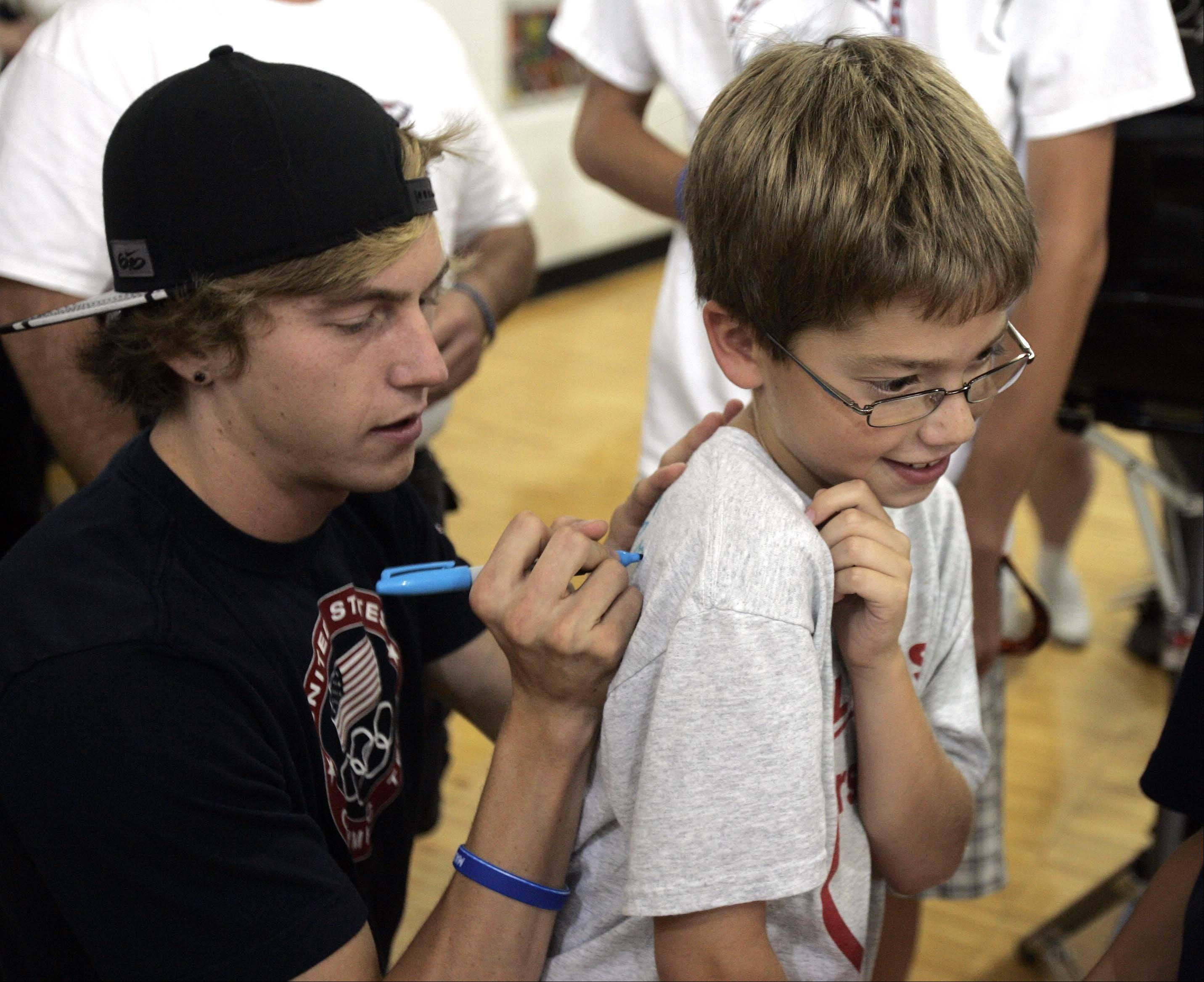 Nine-year-old Logan Marx of Algonquin gets his shirt signed by Olympian Evan Jager who returned to H.D. Jacobs High School in Algonquin Wednesday September 5, 2012.