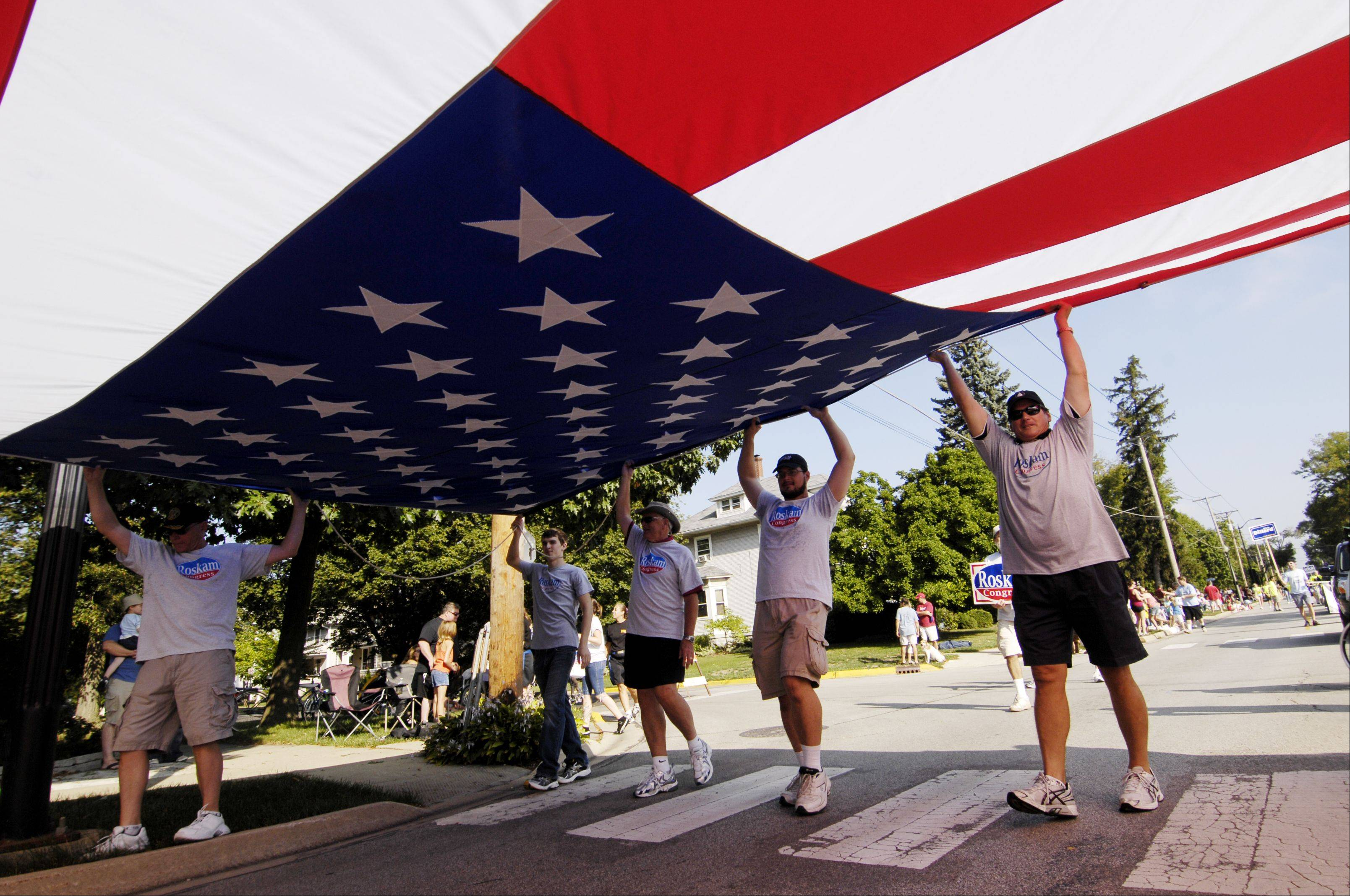 Supporters of Congressman Peter Roskam carry a huge American Flag as they march in the Wheaton Labor Day Parade, Monday. The city of Wheaton holds a Labor Day Parade to make up for the 4th of July parade that was canceled because of storm damage.