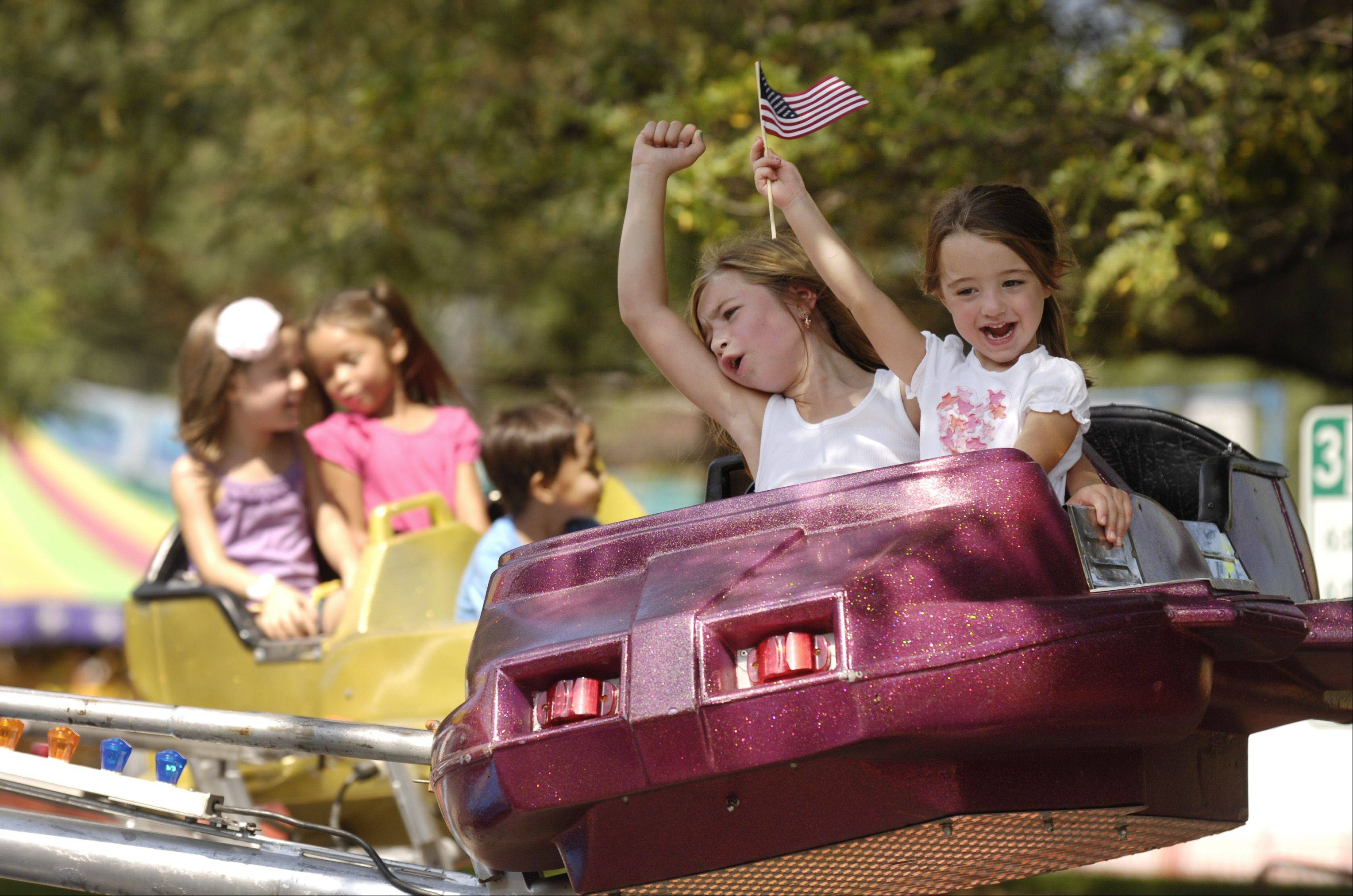 Peyton and Lexi Gilchrist of Naperville enjoy a ride at the annual Naperville Last Fling festival, Monday.