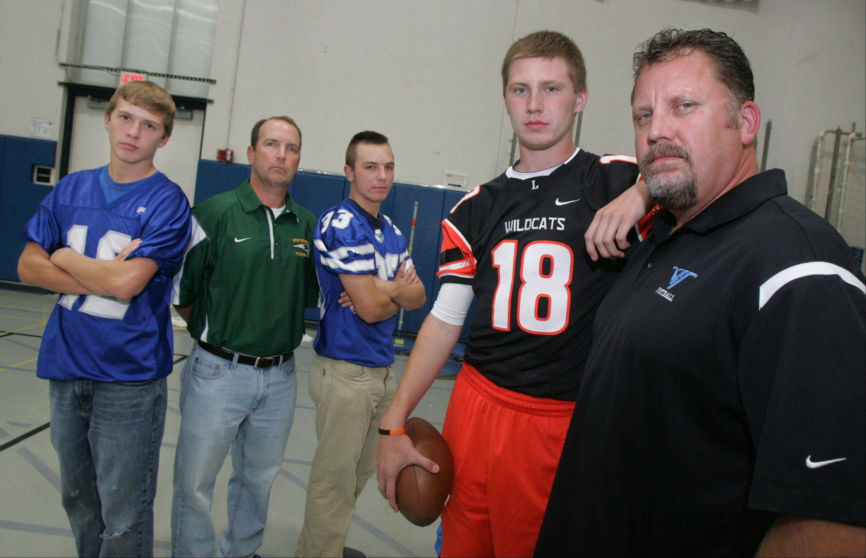 Vernon Hills football coach Tony Monken, right, with his son, Anthony, who plays for Libertyville; and Stevenson football coach Bill McNamara, in green, with his two sons, Dylan (33) and Connor (12), who play for Vernon Hills.