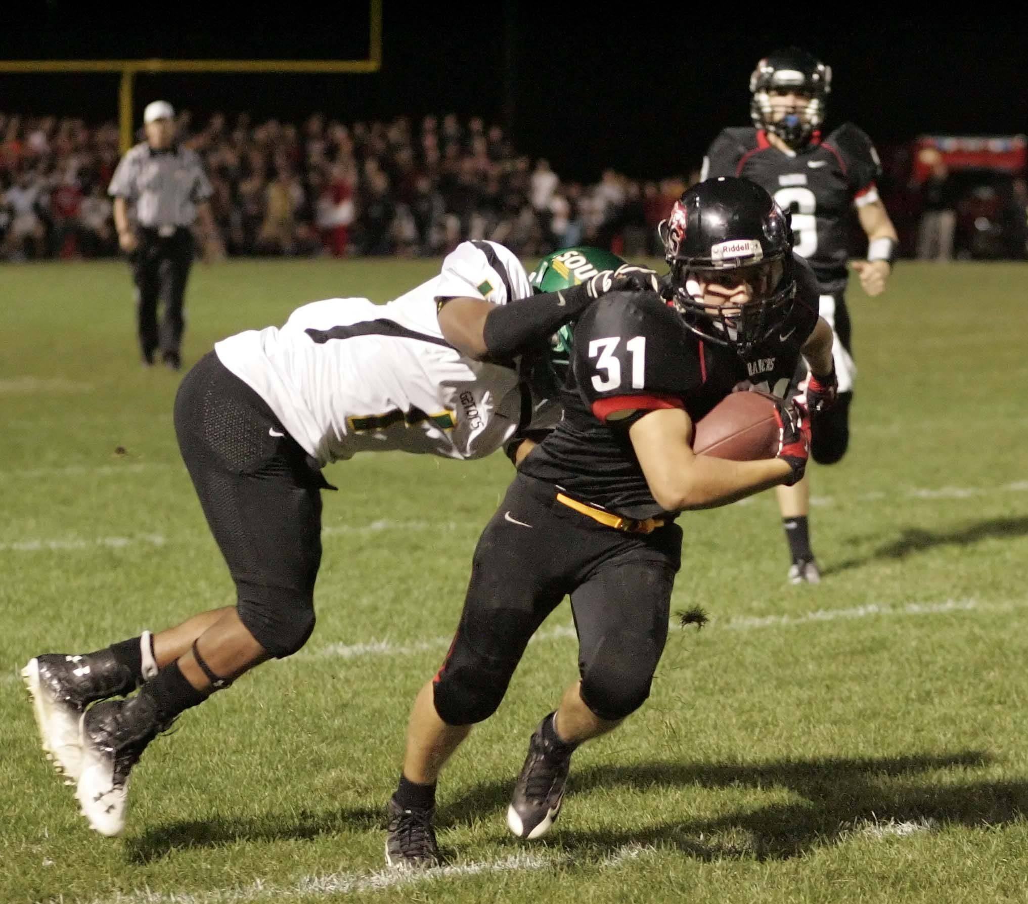 Huntley's Jake Scalise moves upfield as Crystal Lake South's Zevin Clark tries to pull him down Friday night in Huntley.