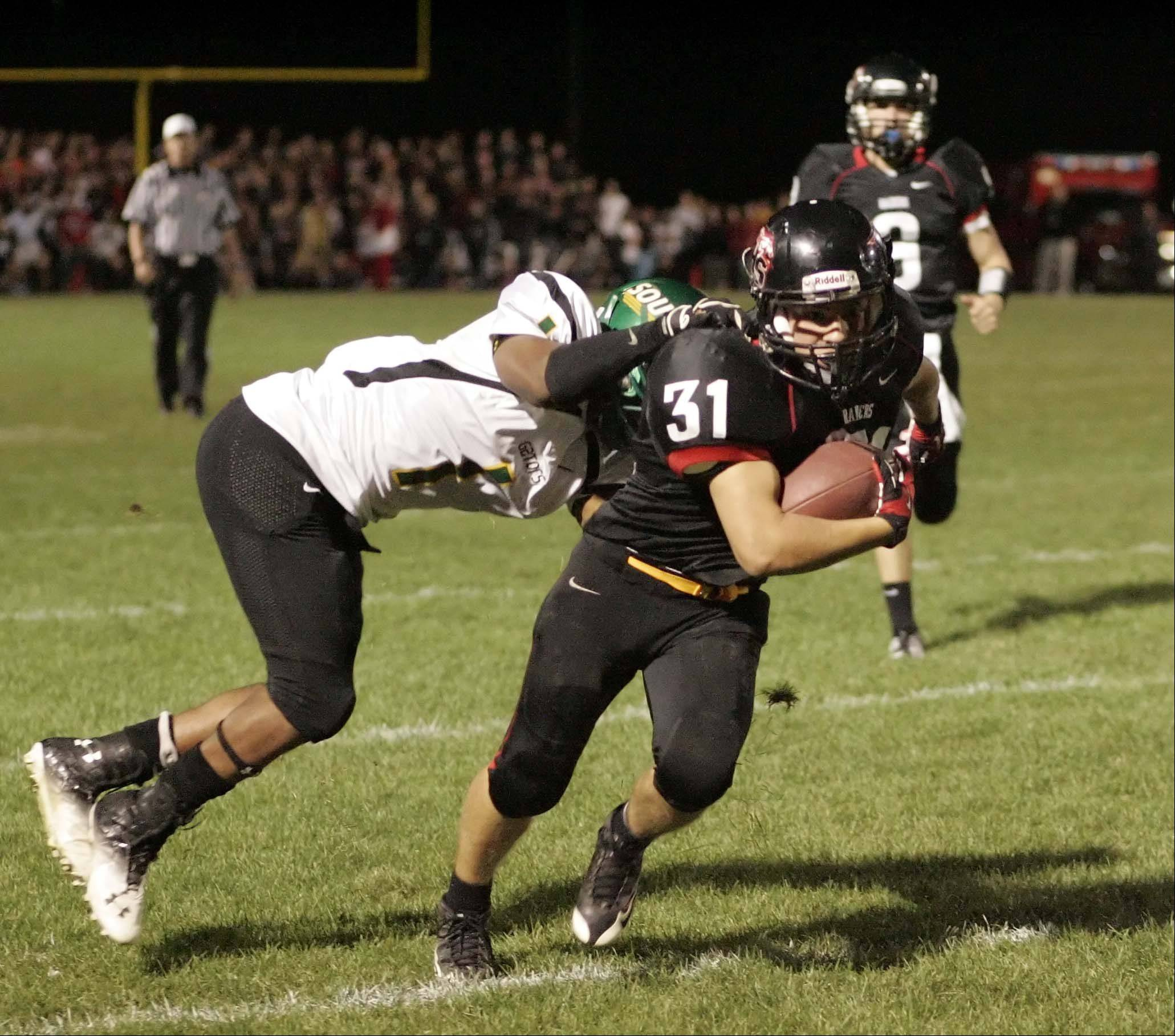 Huntley's Jake Scalise moves upfield as Crystal Lake South's Zevin Clark tries to pull him down .