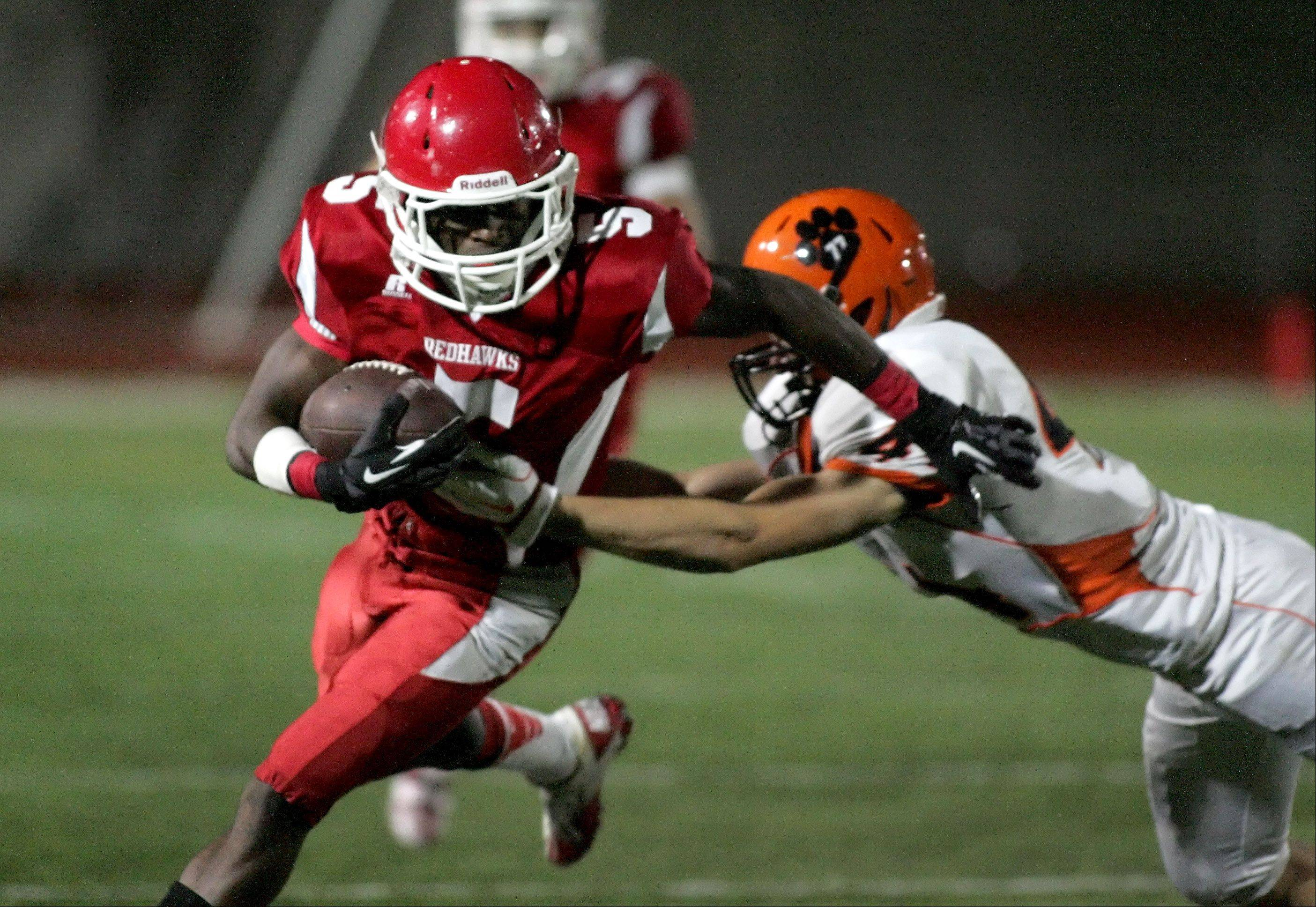 Bev Horne/bhorne@dailyherald.com Lasoda Thompson of Naperville Central eludes a tackle by Wheaton Warrenville South in football action on Friday in Naperville.