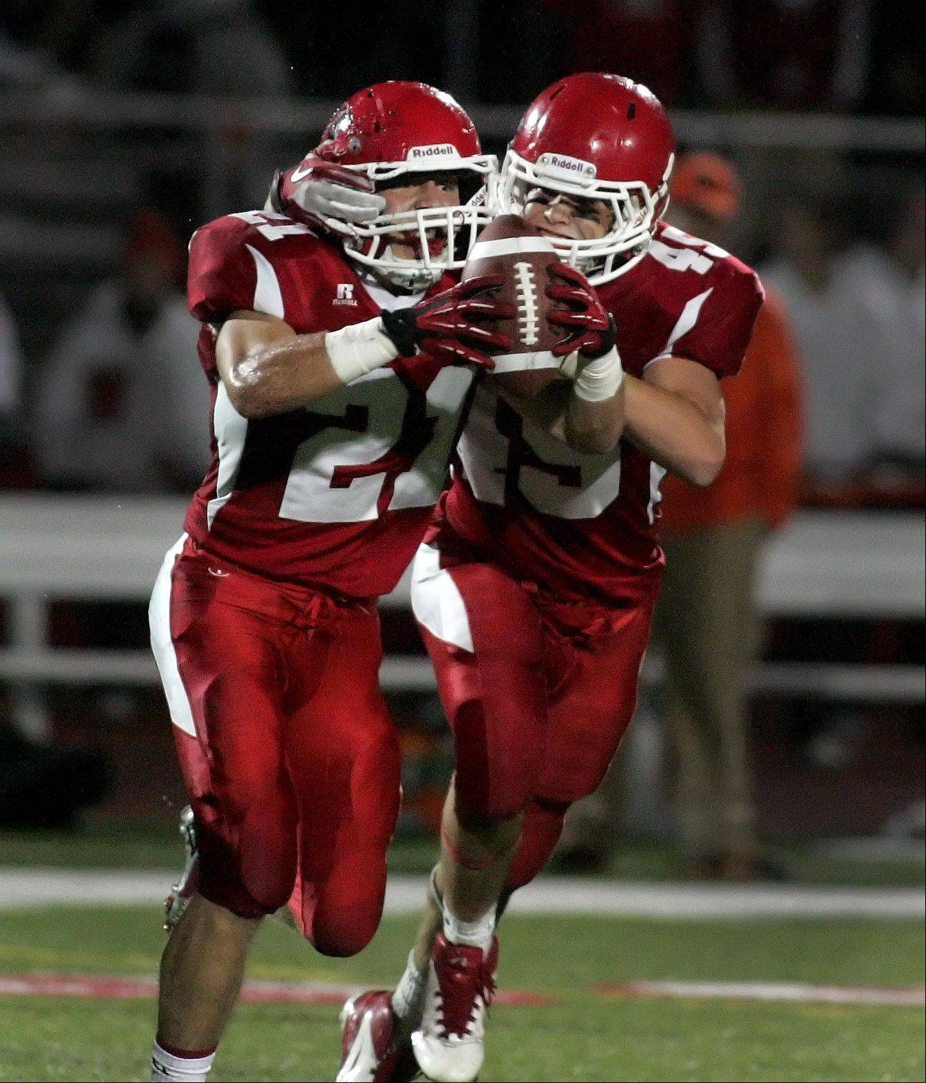 Justin Markham, left, and Jack Wooldridge of Naperville Central, celebrate an interception by Markham against Wheaton Warrenville South.