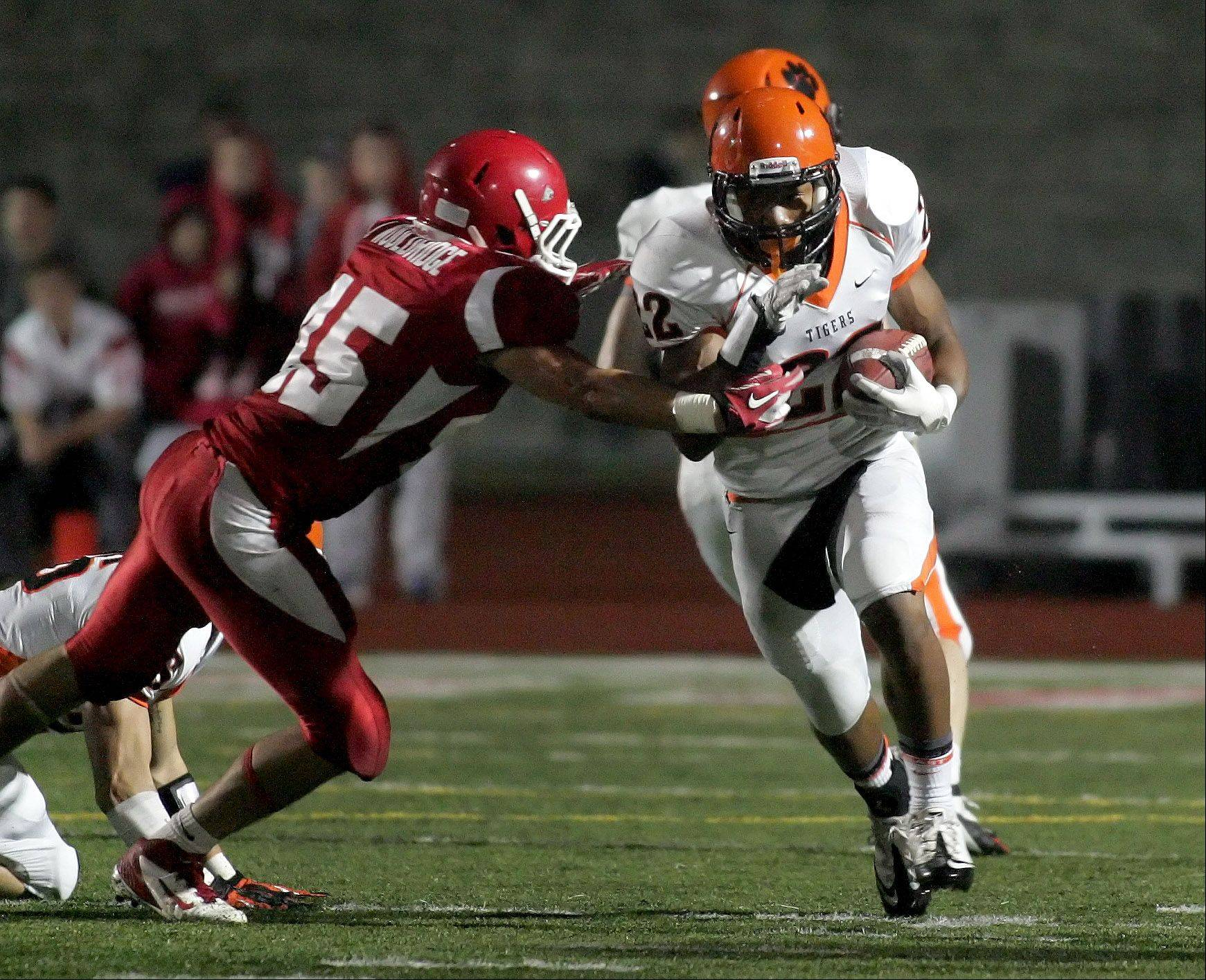 Jack Wooldridge of Naperville Central, left, moves in to tackle Brandon Adams of Wheaton Warrenville South.