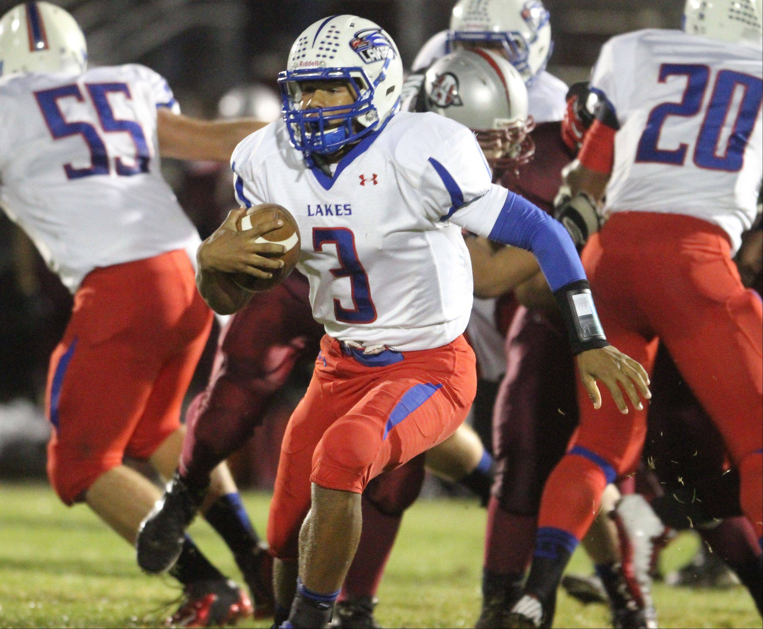 Lakes quarterback T.J. Edwards rushes the ball against Antioch .
