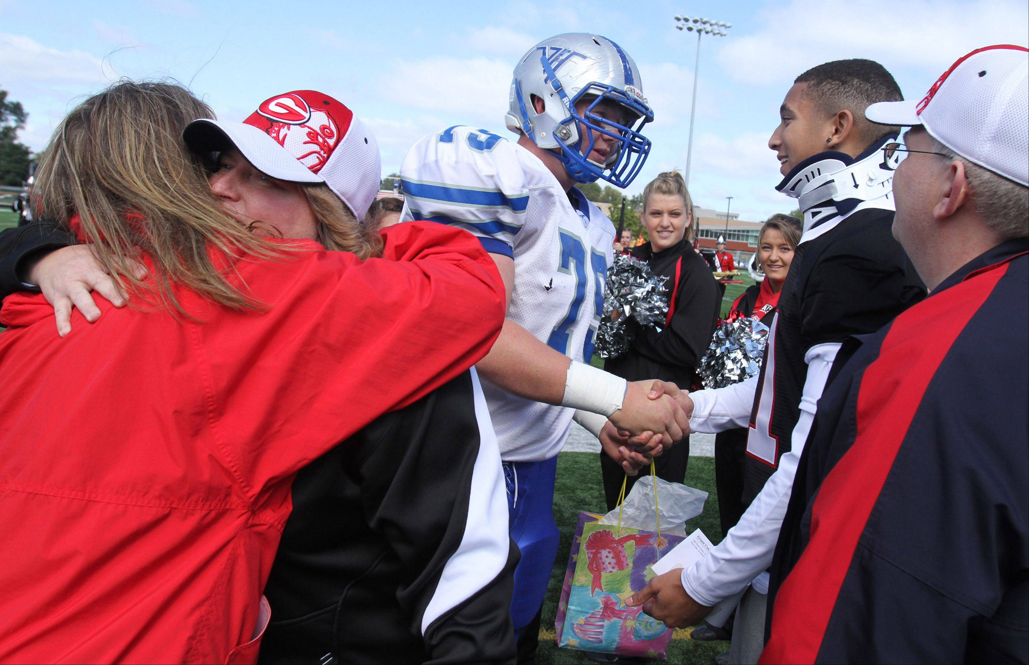 Grant cornerback Chris Gomoll receives a gift and a handshake from Vernon Hills offensive lineman and team captain Drake Randall, as Gomoll's dad Ray looks on and his mom Angie receives a hug before the school's game against Vernon Hills last Saturday.