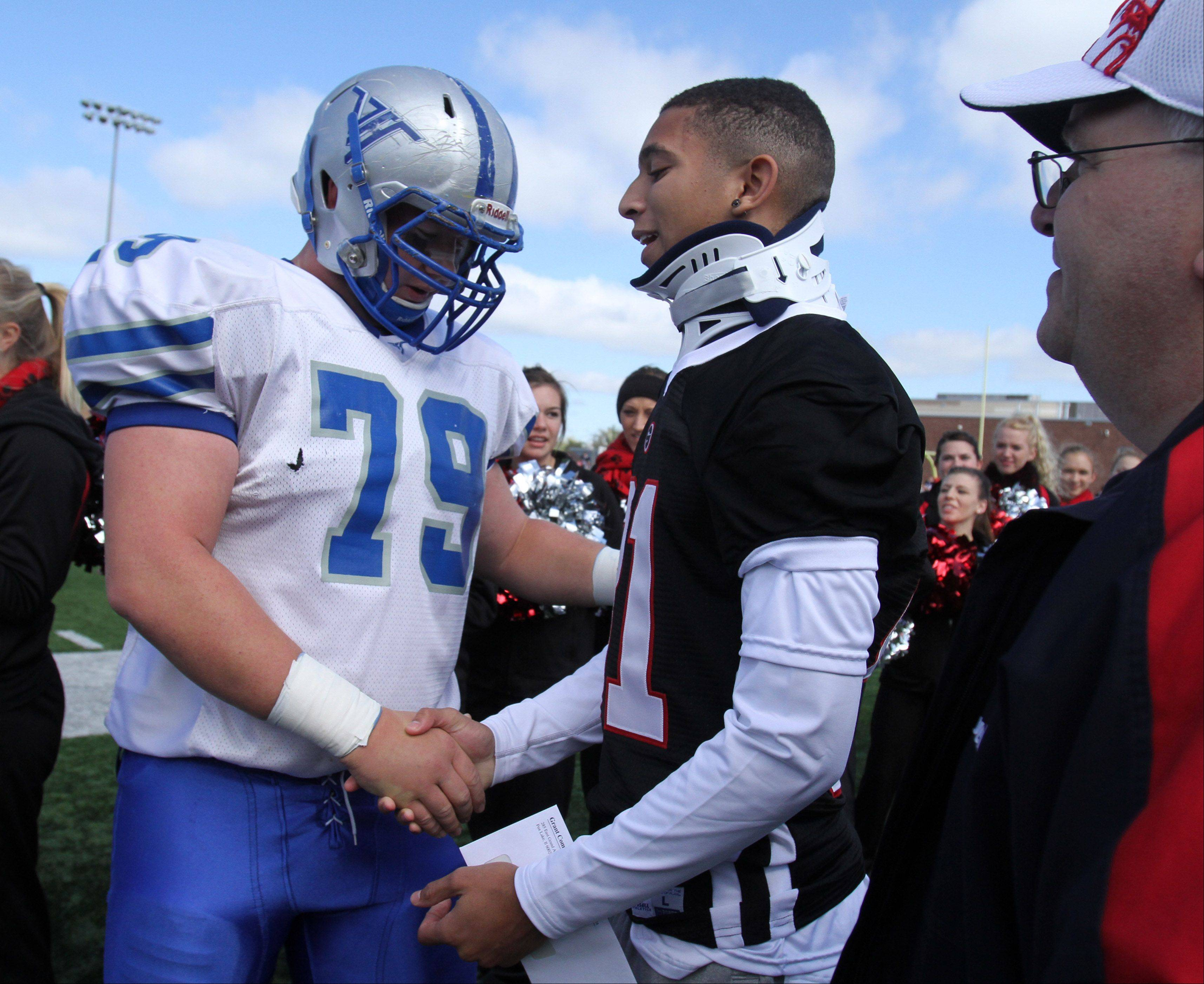 Grant cornerback Chris Gomoll, right, receives a gift and handshake from Vernon Hills offensive lineman and team captain Drake Randall, as Gomoll's dad, Ray, looks on before Grant's homecoming game last Saturday.