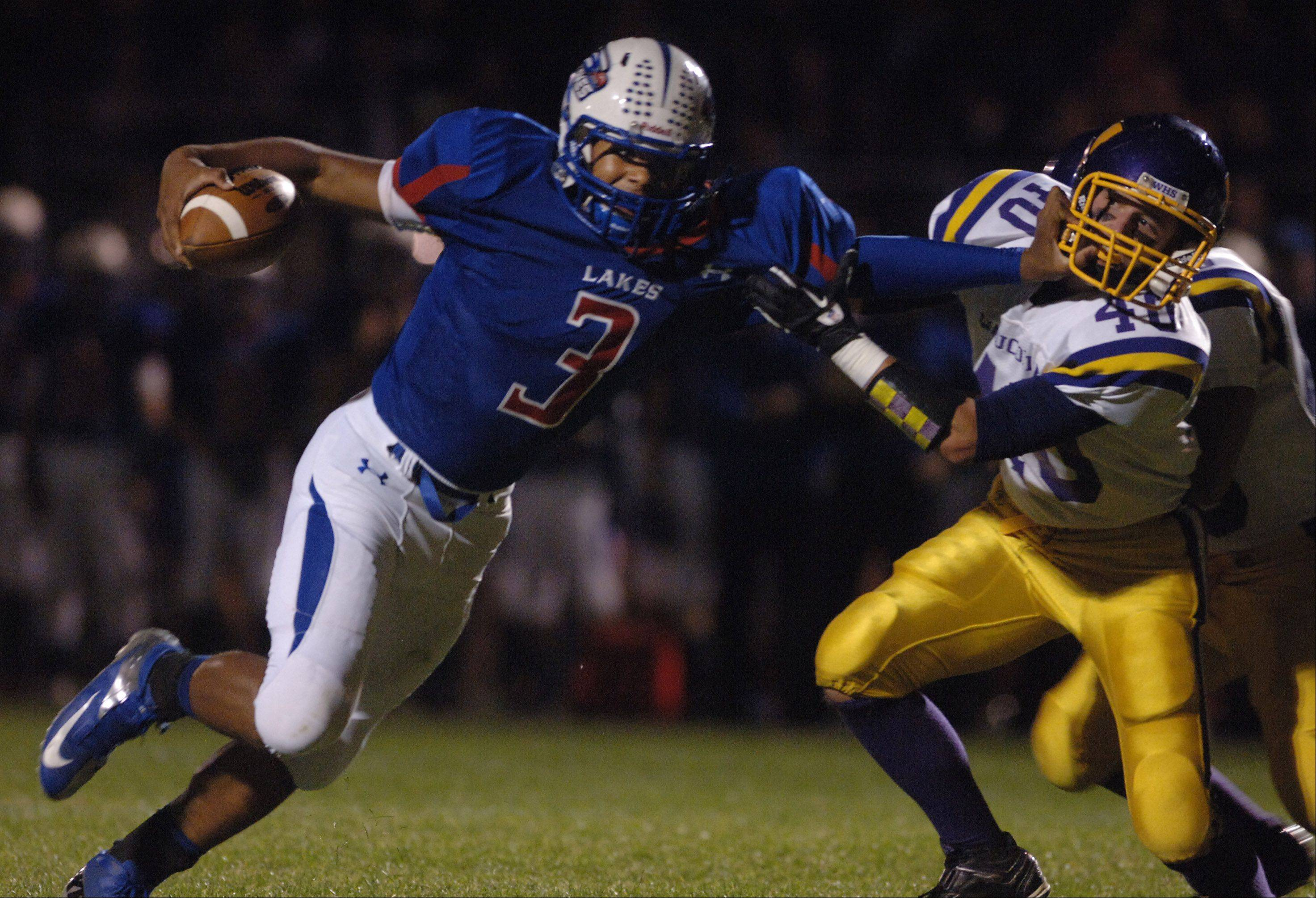 Lakes' T. J. Edwards (3) gives Wauconda's Elliot Hill a shove as he runs a play Friday in Lake Villa.