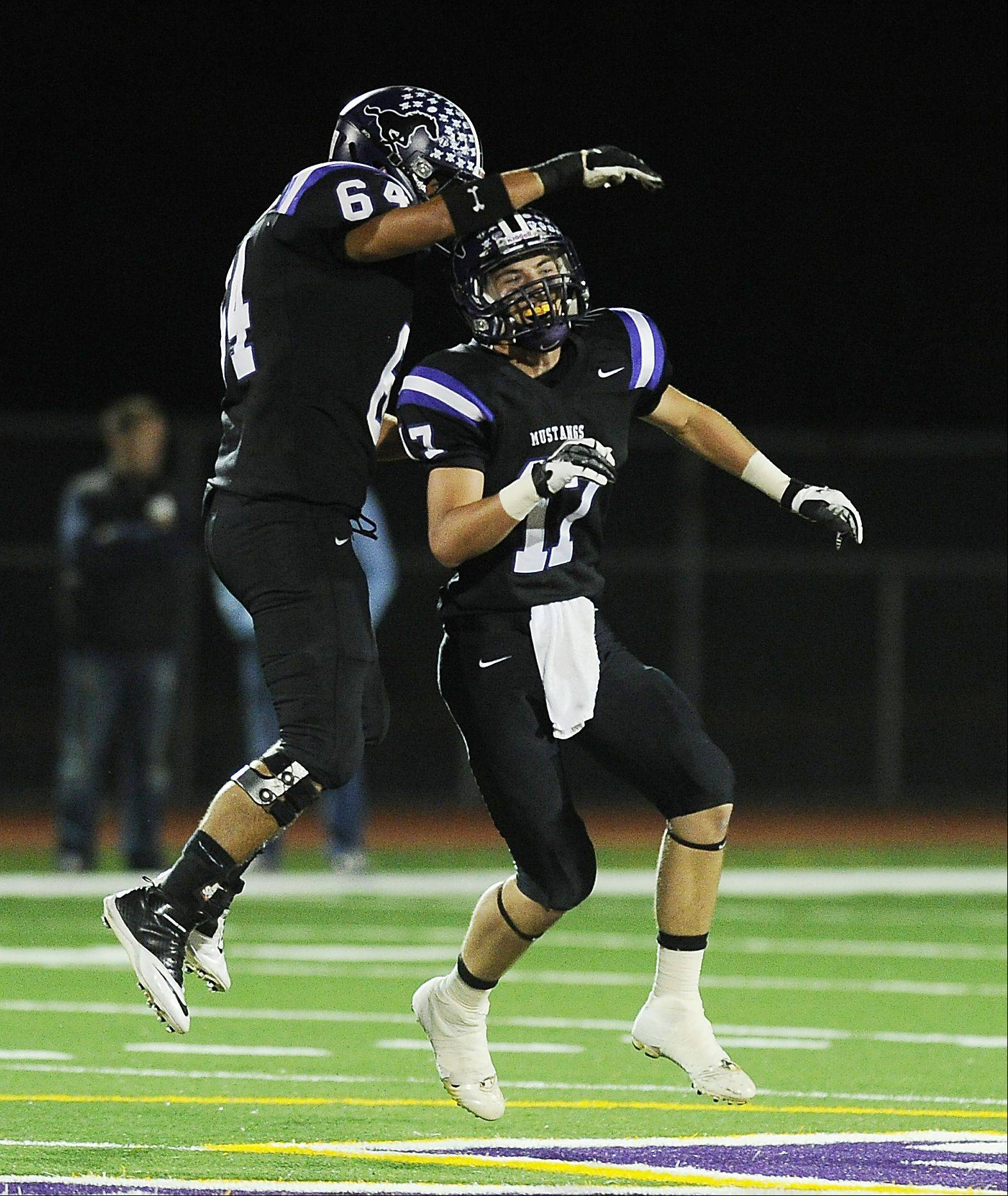 Rolling Meadows' Jacob Grant celebrates a sack of Prospect's quarterback Devin O'Hara with Mustang teammate Raul Alba-Cortez in the first half.