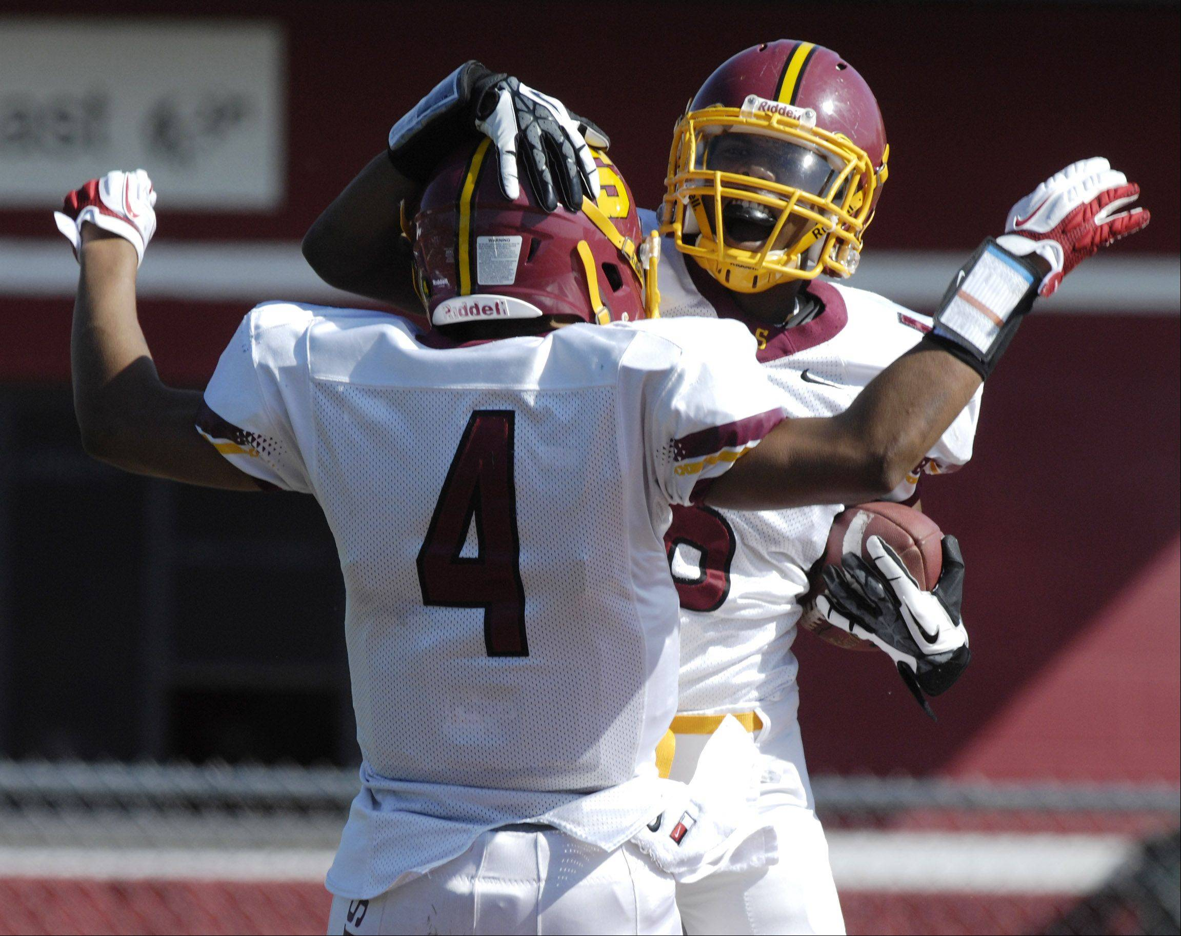 JOE LEWNARD/jlewnard@dailyherald.com Schaumburg's Juwaan Richard, right, celebrates his first-quarter touchdown with teammate Akema Collins during Saturday's game against Barrington.