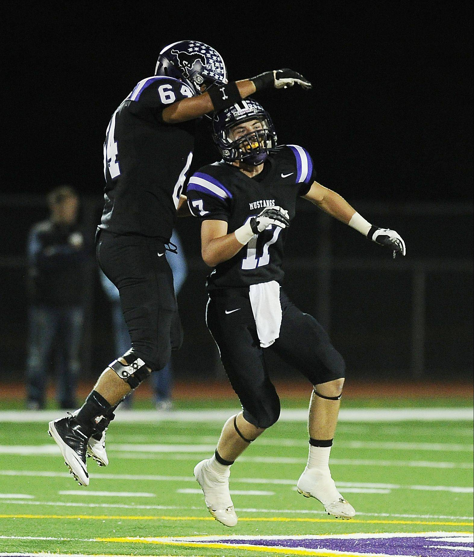 Rolling Meadows' Jacob Grant celebrates a sack with teammate Raul Alba-Cortez against Prospect on Friday at Rolling Meadows.