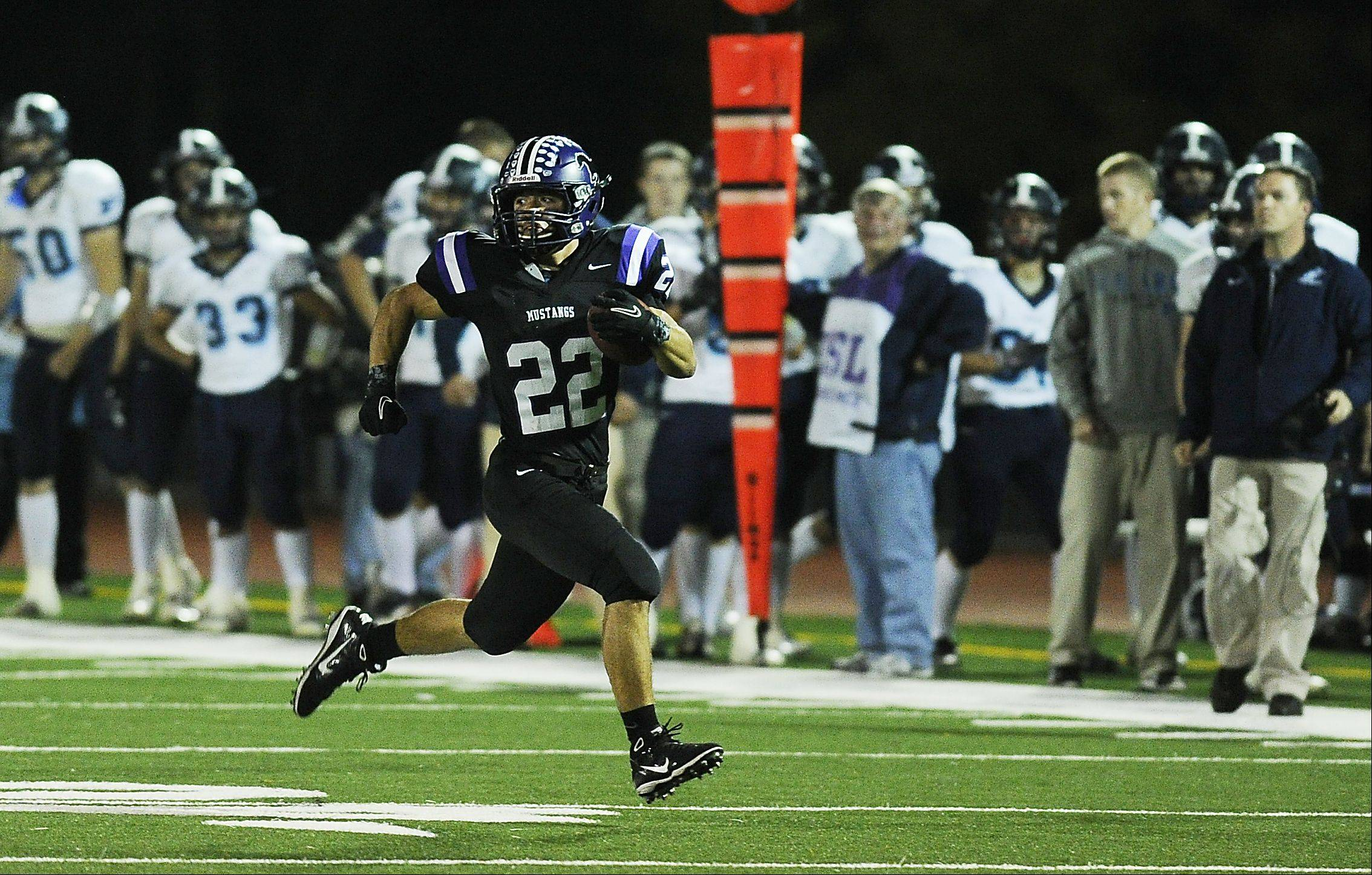 Rolling Meadows' Steven Royster looks behind him with nothing but open space in front on his way to a first-half touchdown against visiting Prospect on Friday.