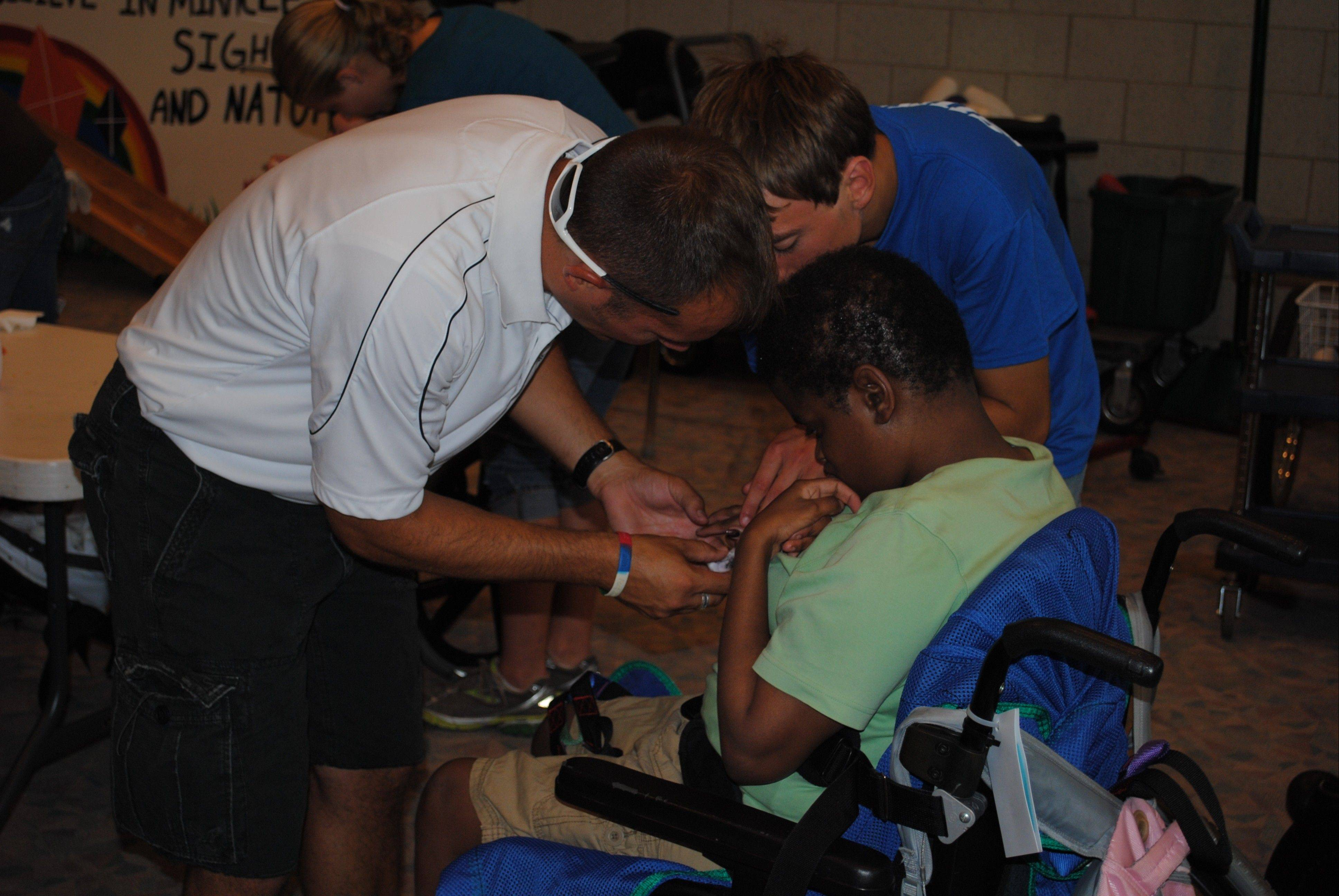 Kaneland boys cross country coach Chad Clarey and a team member paint the nails of a Marklund client during a recent visit.