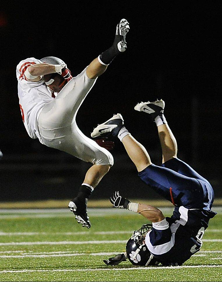 Palatine receiver Alex Nawrot goes flying over Conant's Kramer Brandt late in the second quarter on a reception Friday at Conant in a key Mid-Suburban West matchup.