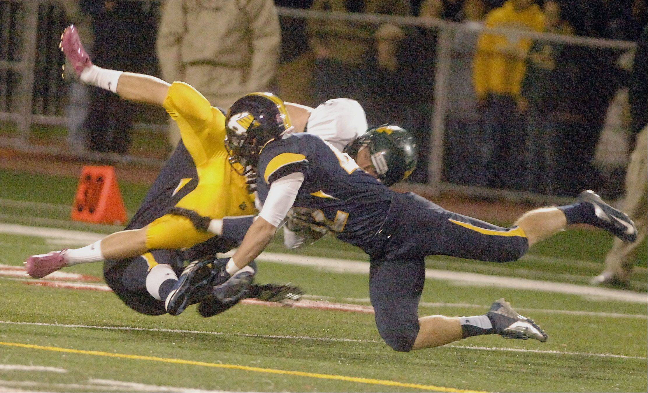 Dan Waldron of Waubonsie Valley High School is pulled down by Spencer Donahue of NeuquaValley High School.