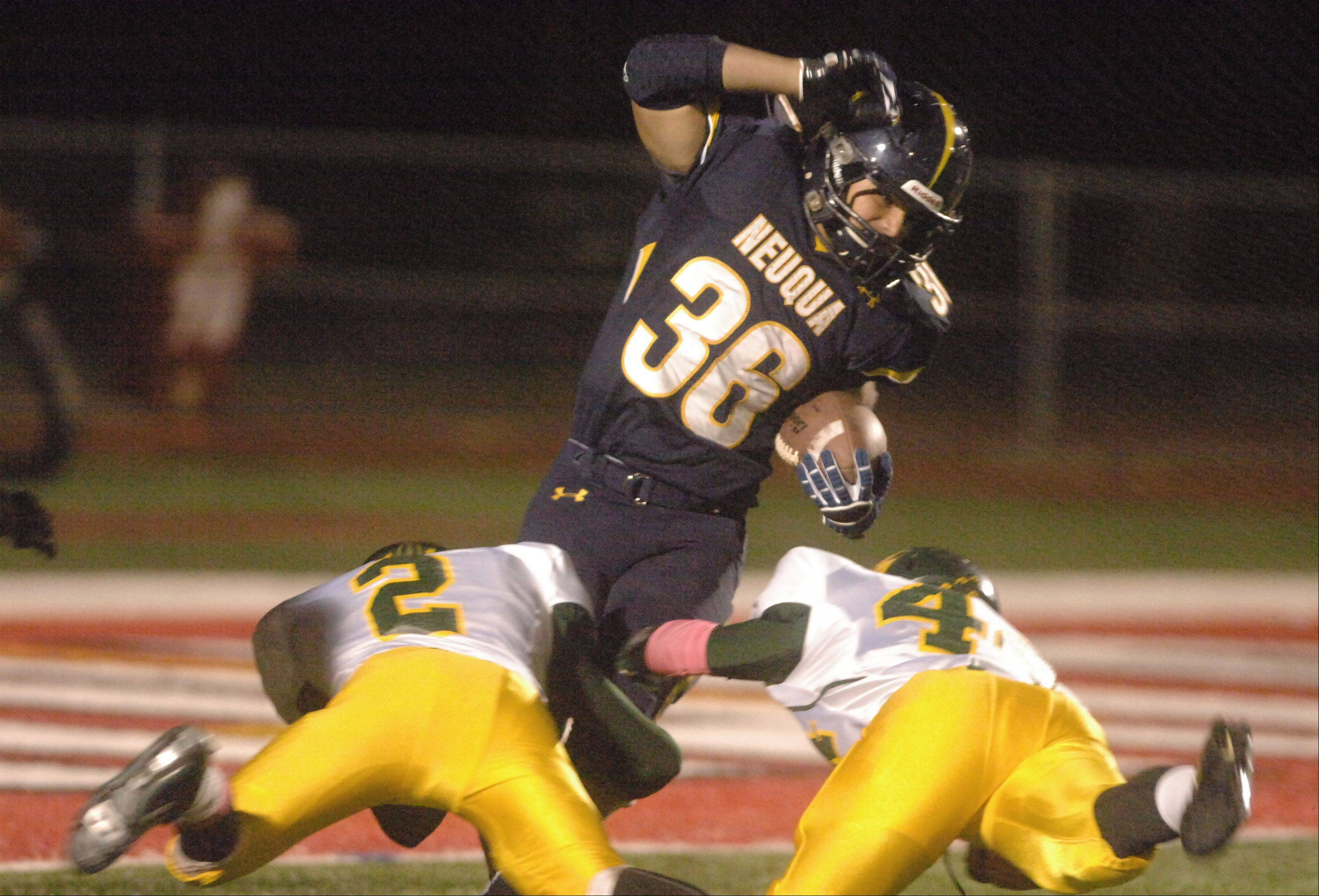 Joey Rhattigan of Neuqua Valley,center, is pulled down by Brock Westwood and Connor Ihry.