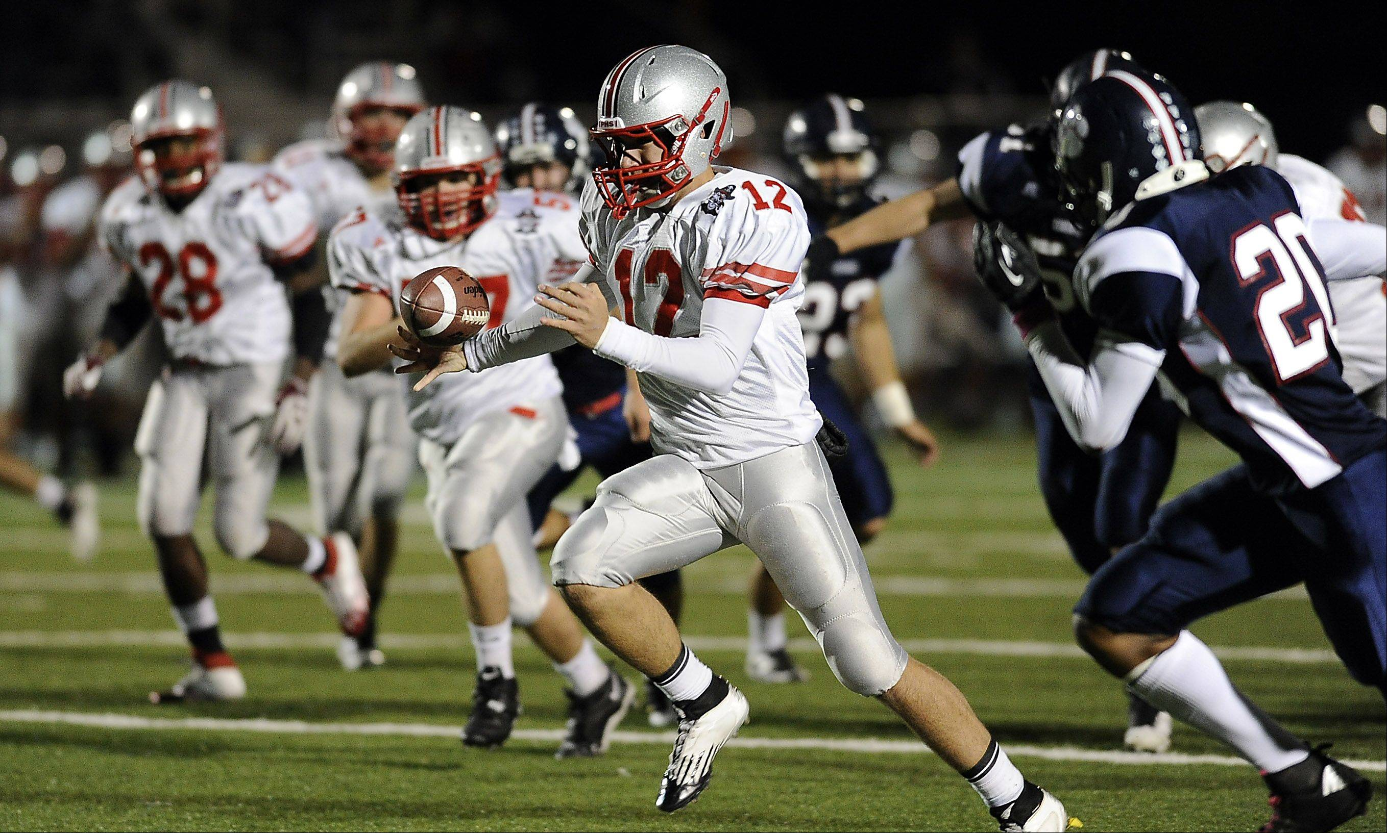Palatine's quarterback Ethan Olles tries to maintain control of the ball as he runs.