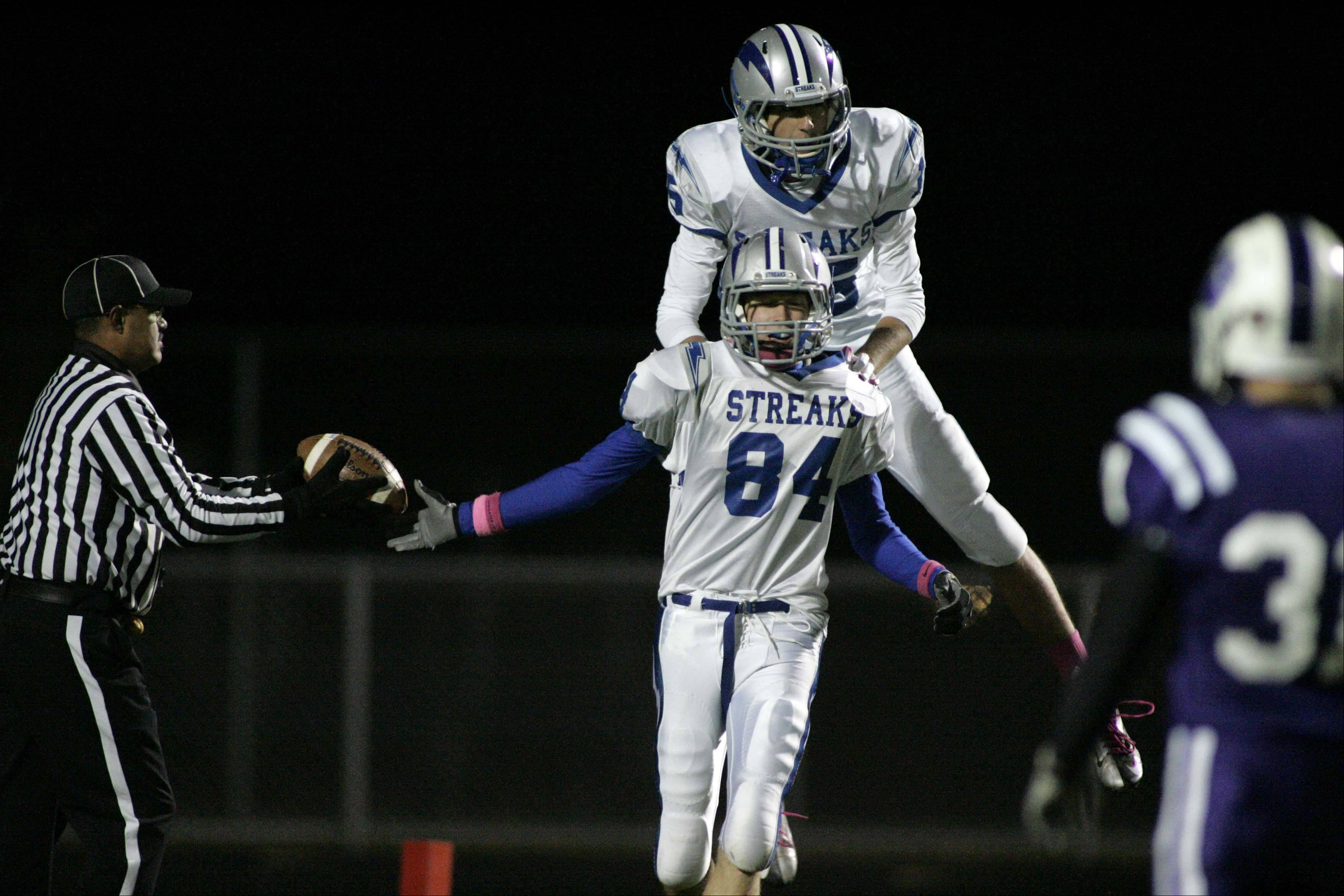 Woodstock's Matthew Swedberg is greeted by Mitch Kohley after a touchdown.