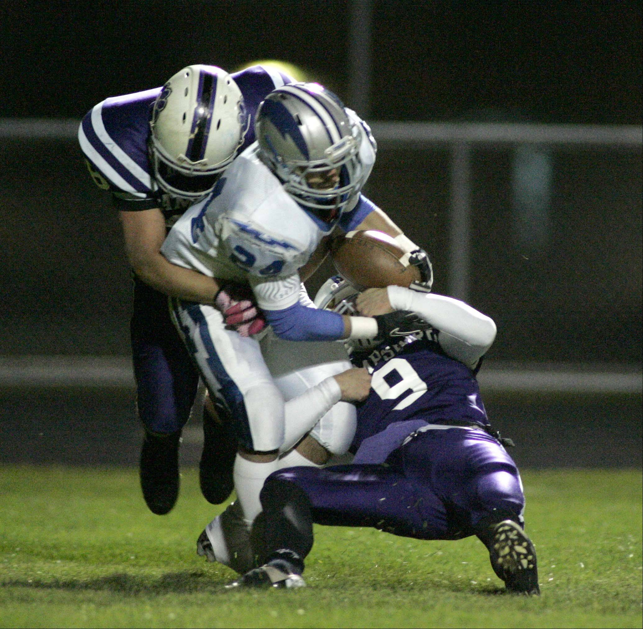 Hampshire's Philip LaPointe and Kyle Anderson bring down Woodstock's Mike Santucci for a safety in the first quarter.