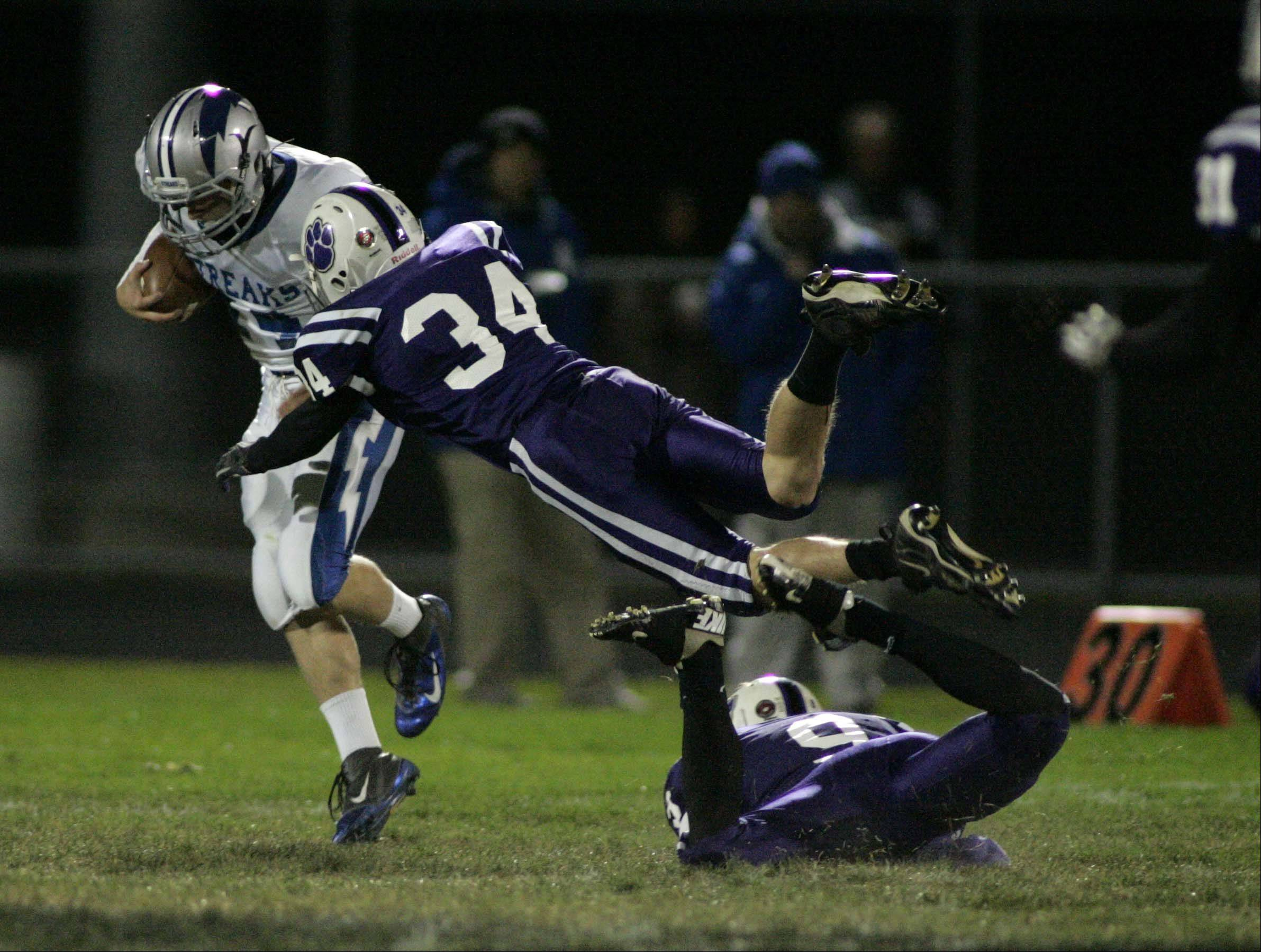 Hampshire's Brendan Waterworth and Kyle Anderson try to bring down Woodstock's Alan Hafer after an interception.