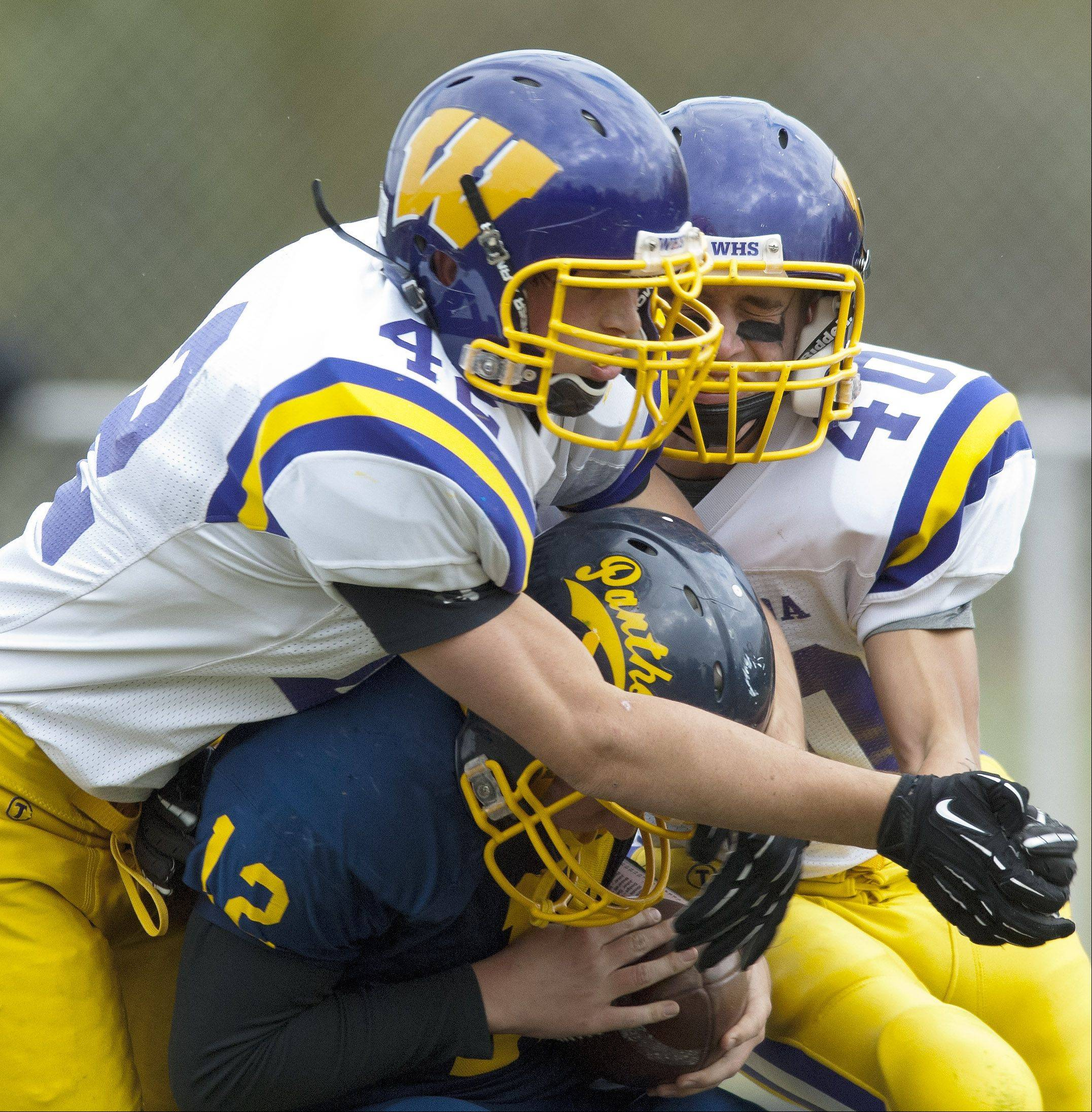 Round Lake quarterback John Ridley gets sacked by Wauconda's Graham Miller, left, and Elliot Hill.