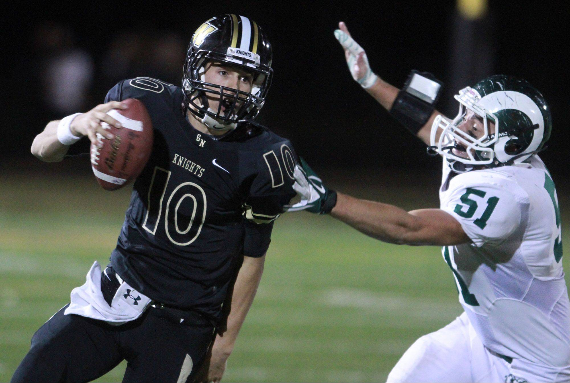 Grayslake North quarterback AJ Fish slips past Grayslake Central defender Alex McCully.