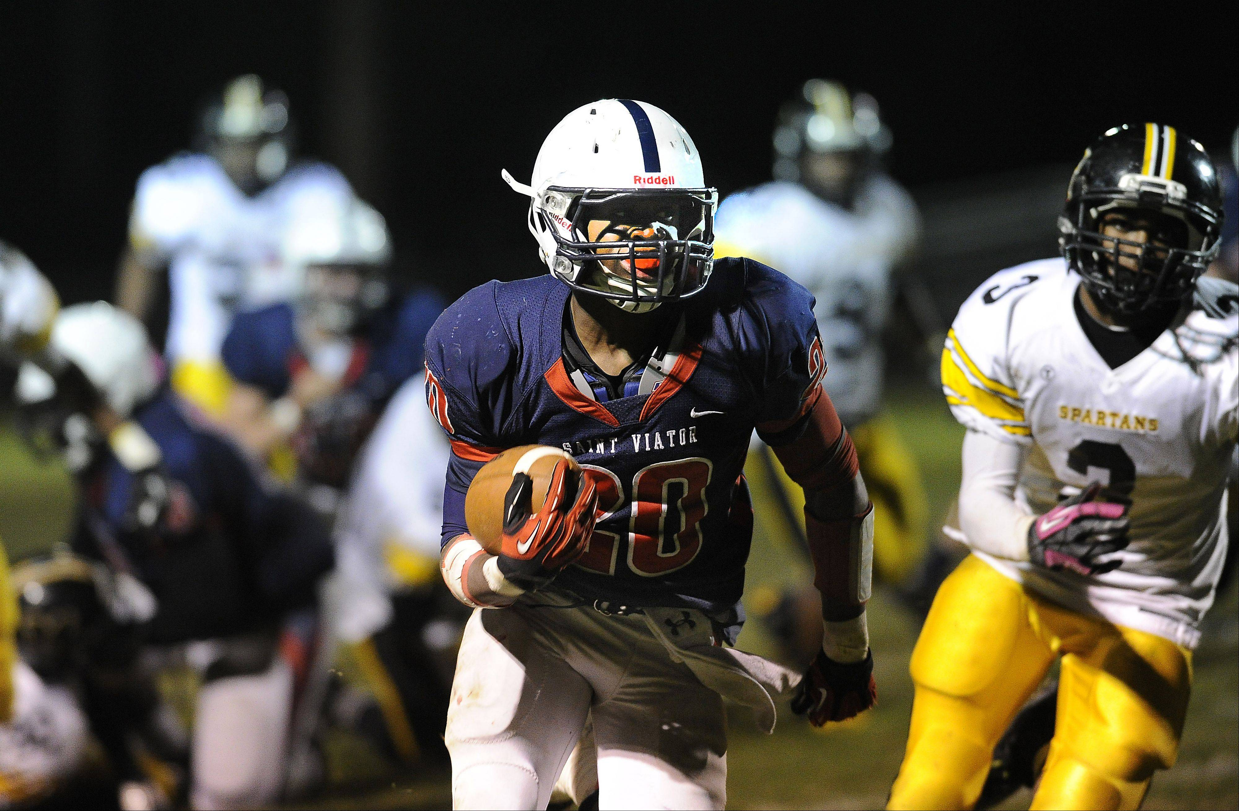 Mark Welsh/mwelsh@dailyherald.com St. Viator's Mayo Arogundade outruns the Marian Catholic defensive players in the second quarter on this touchdown run at Forest View Educational Center in Arlington Heights on Friday.