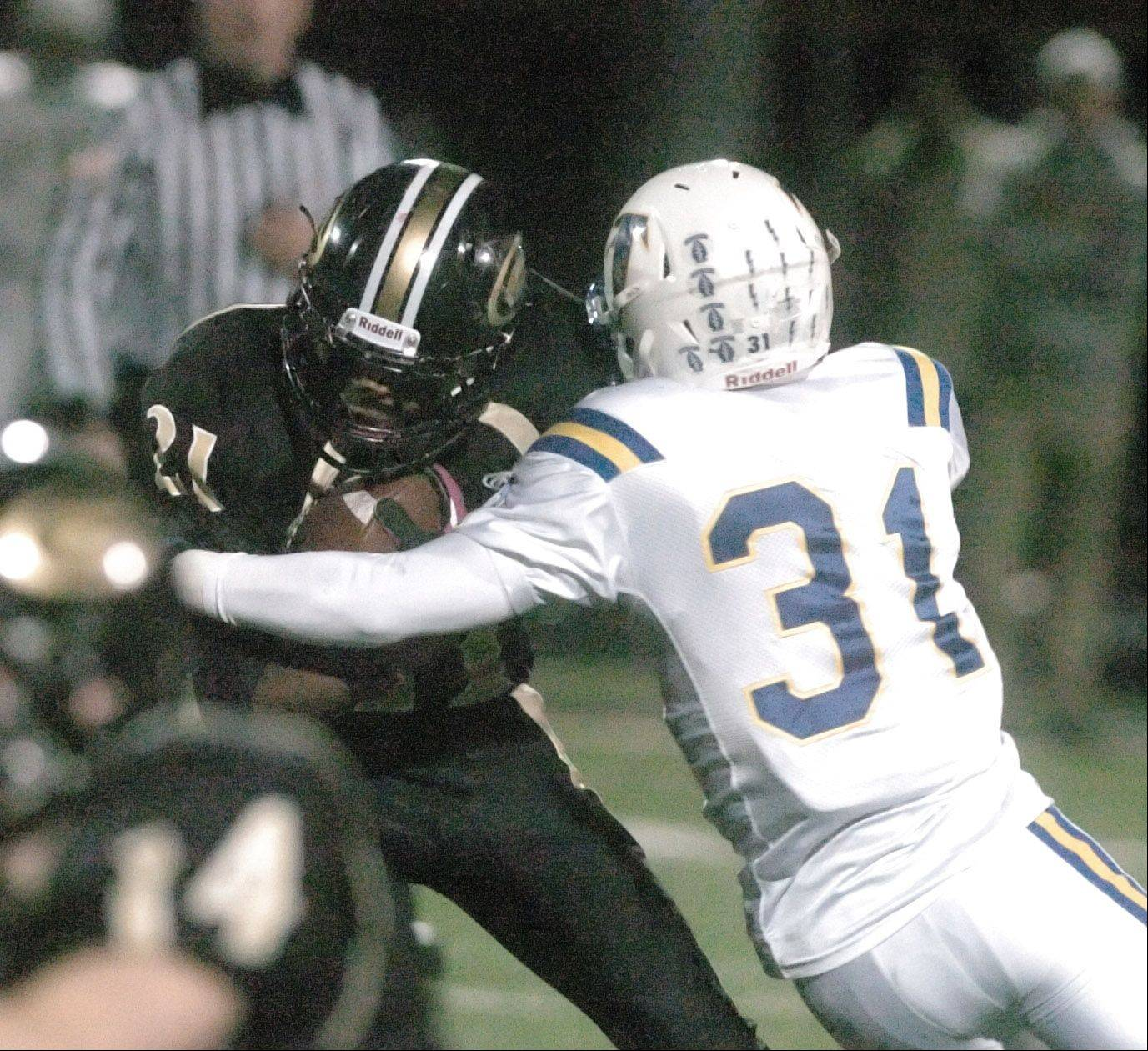 Justin Jackson of Glenbard North moves the ball as Jaylen Howze of Wheaton Norh pulls him down.