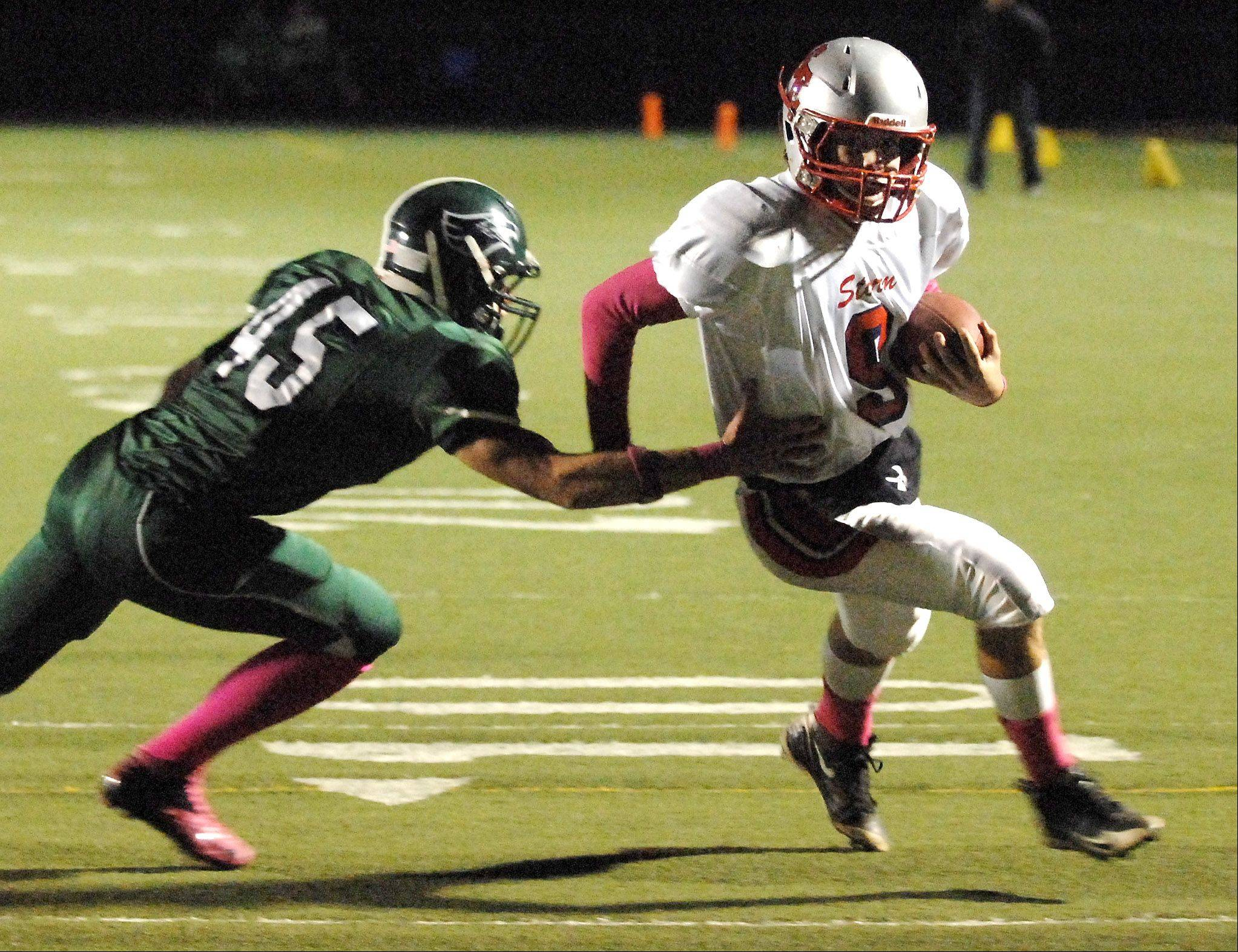 South Elgin's Robert Cuda gets past Bartlett's Chris Janssen en route to an 11-yard touchdown run.