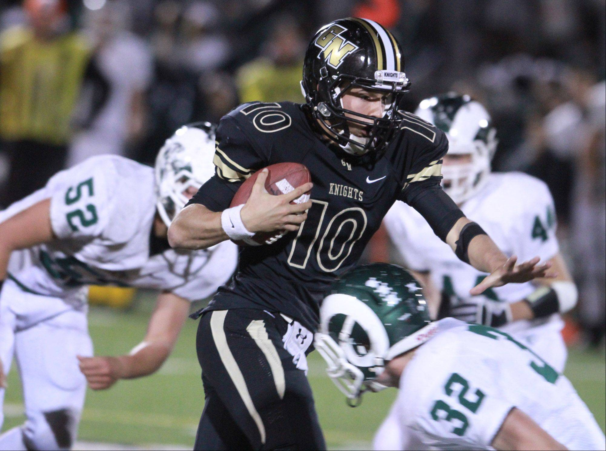 Grayslake North quarterback Anthony Fish slips past several Grayslake Central defenders.