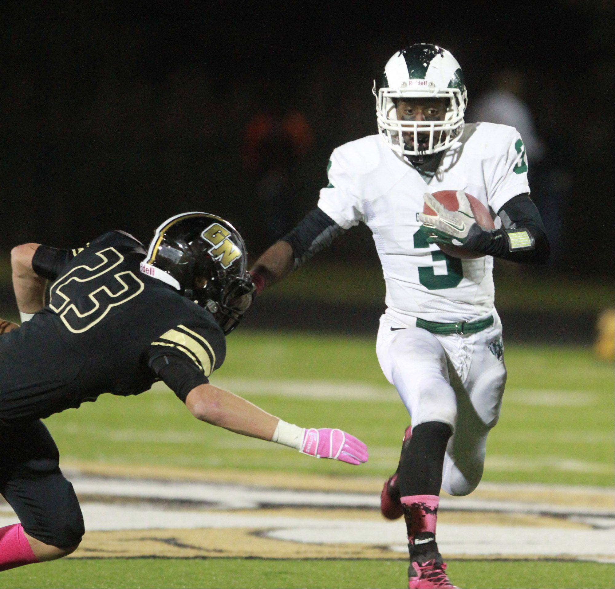 Grayslake Central running back Davonta Jennings looks to runs past Grayslake North defender Spencer Davis.