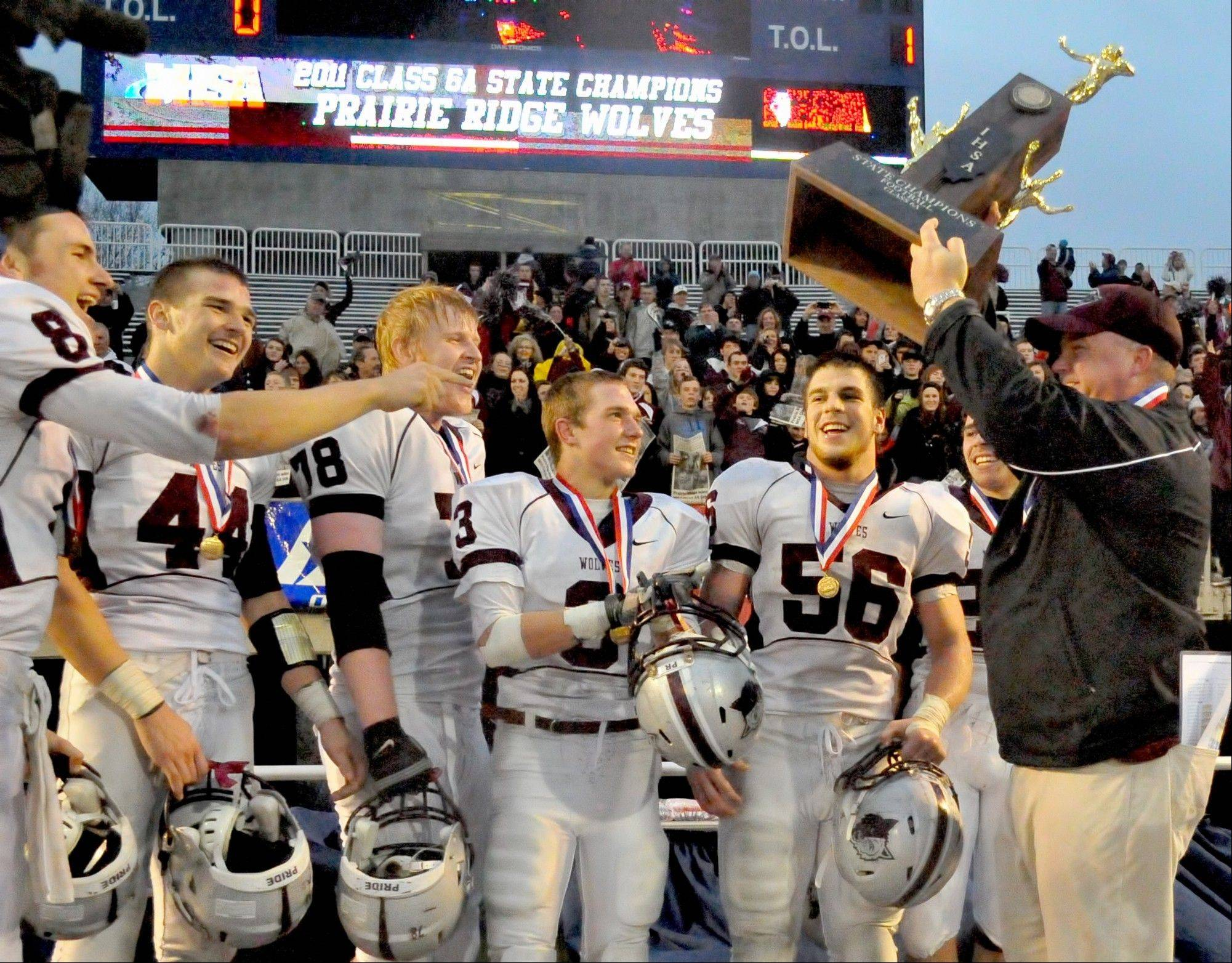 Prairie Ridge head coach Chris Schremp and members of the team accept the championship trophy after beating Richwoods 35-14 during the 2011 IHSA Class 6A high school championship football game at Memorial Stadium in Champaign.