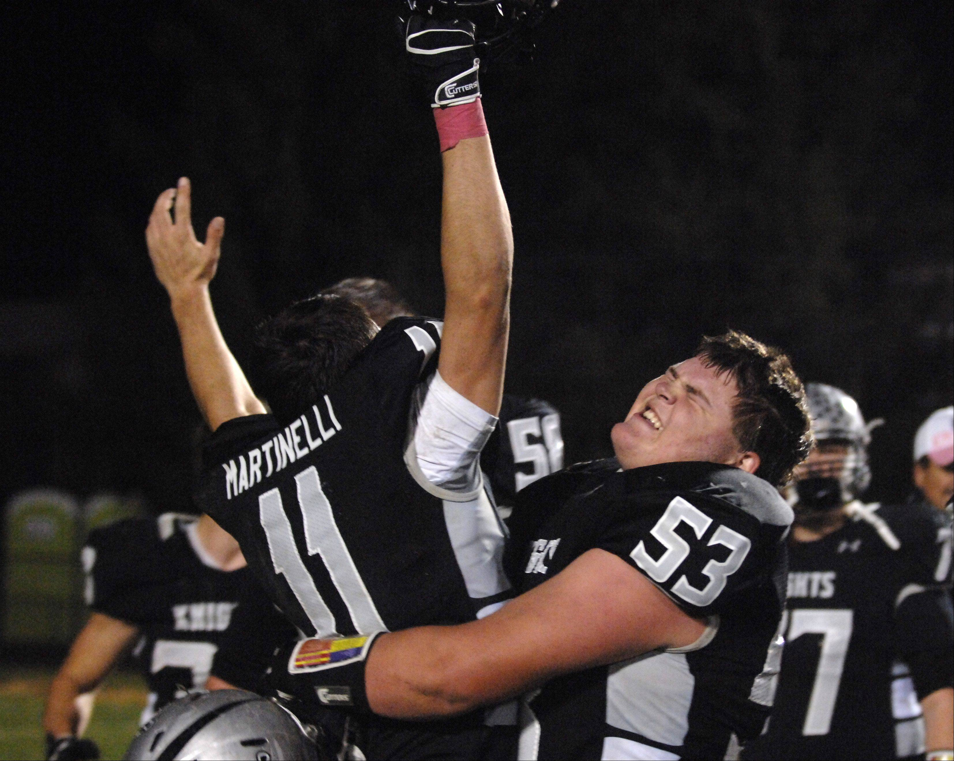 Kaneland's Justin Diddell, right, grabs teammate Zack Martinelli after their win over Morris Friday in Maple Park.