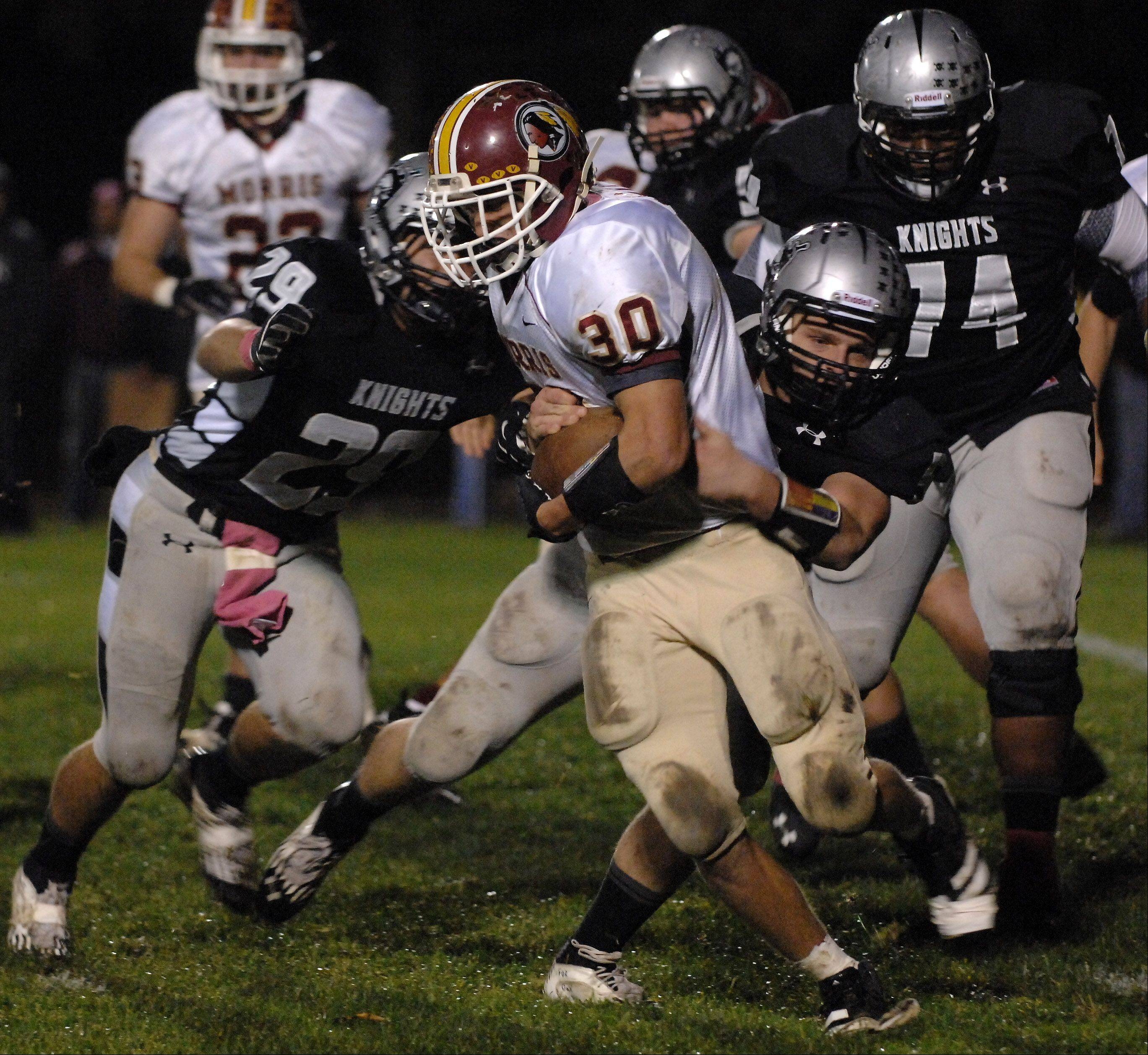 Kaneland's Ryan Lawrence, left, and Gary Koehring, right, bring down Morris' Reese Sobol during Friday's game in Maple Park.