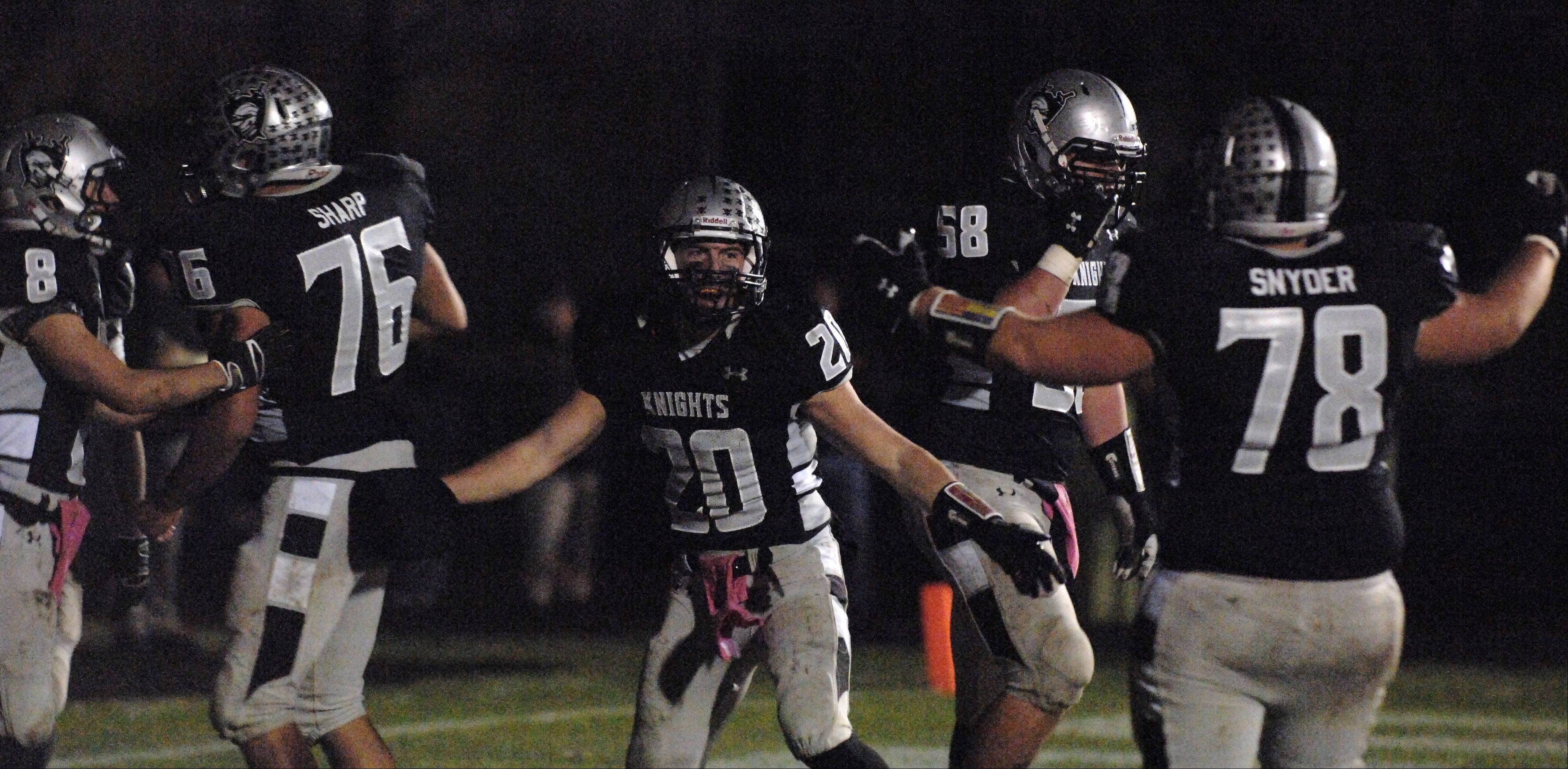 Kaneland's Dylan Nauert (20) and his teammates celebrate his touchdown during Friday's game in Maple Park.