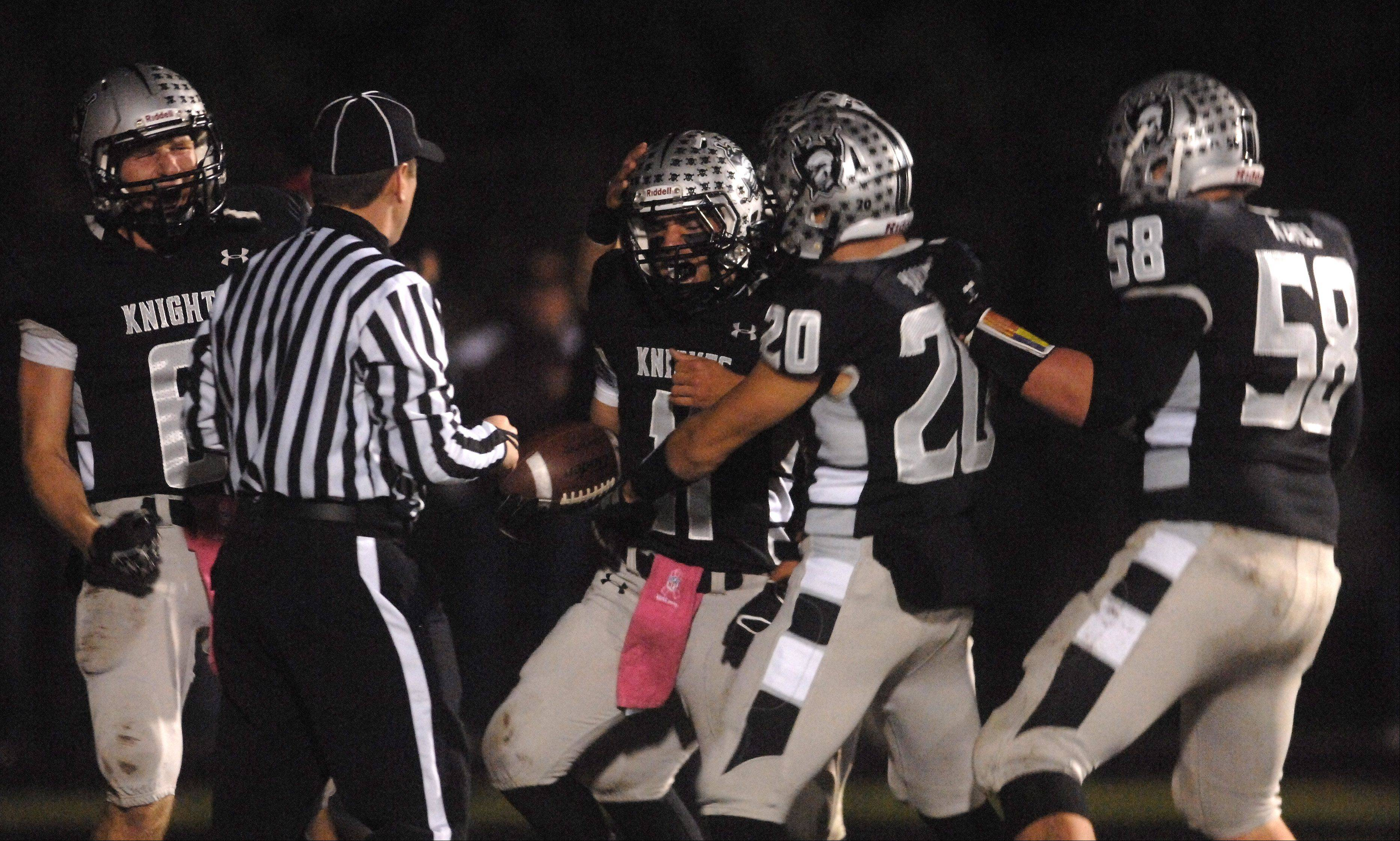 Teammates congratulate Kaneland's Zack Martinelli after a touchdown during Friday's game in Maple Park.