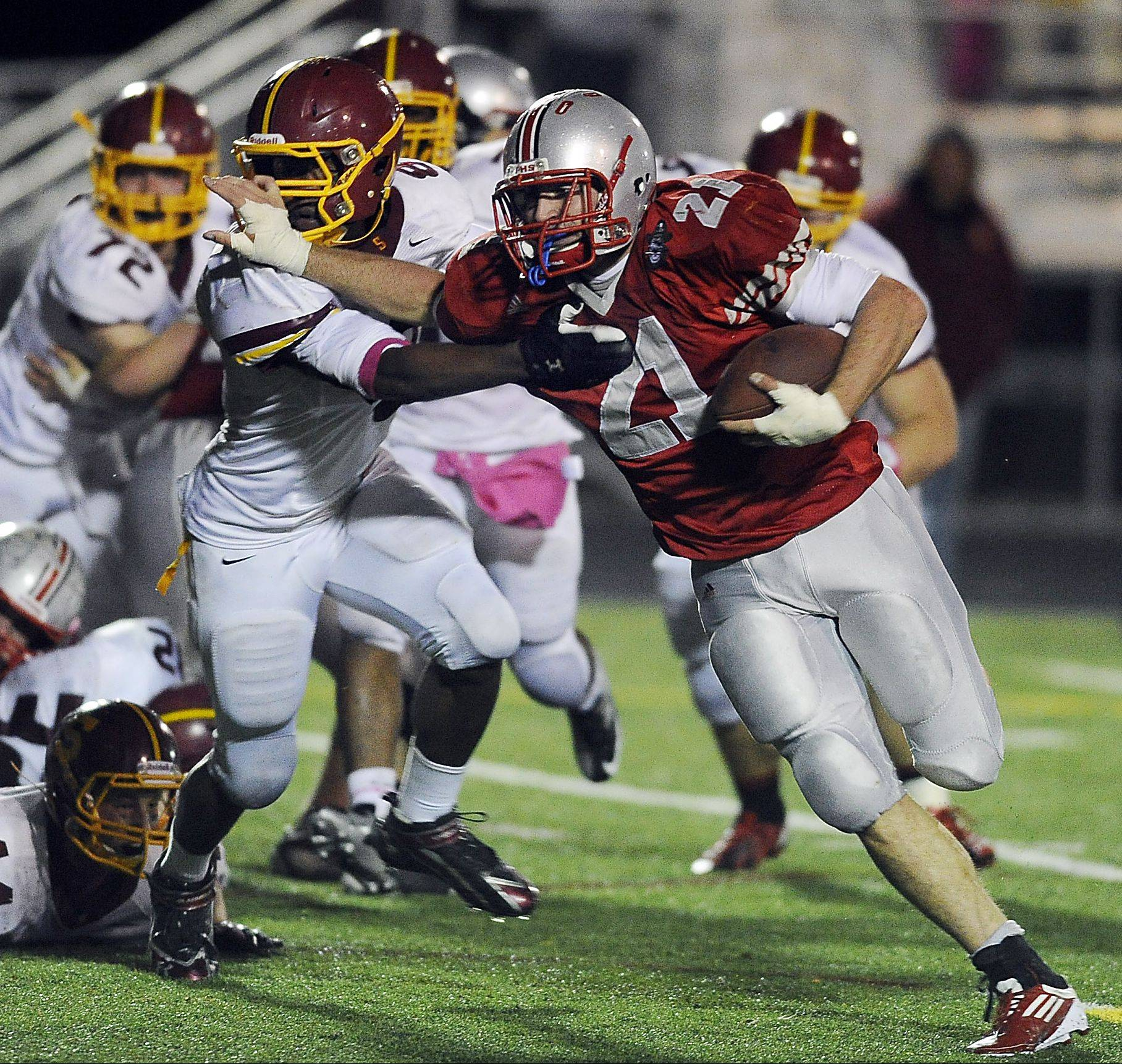 Palatine's John Serio fights off a Schaumburg defender on a first-half touchdown run to help the Pirates top Schaumburg 51-18 and clinch an outright championship in the Mid-Suburban West.