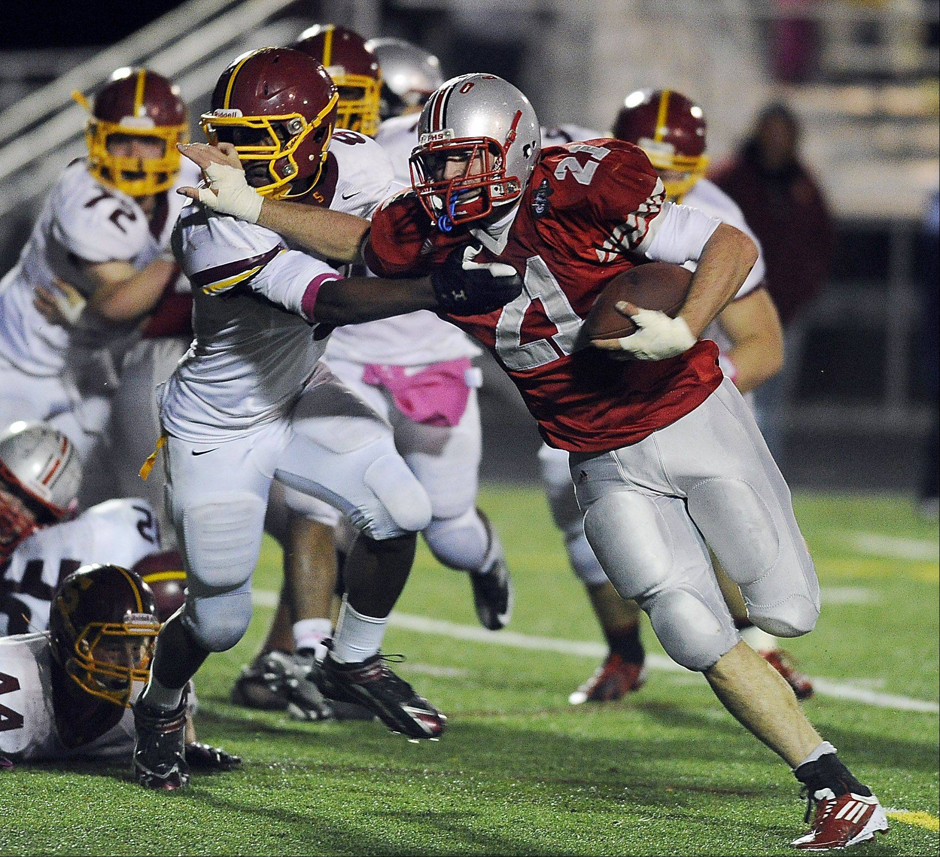 Palatine's John Serio fights off a Schaumburg defender in the first half to score a touchdown.