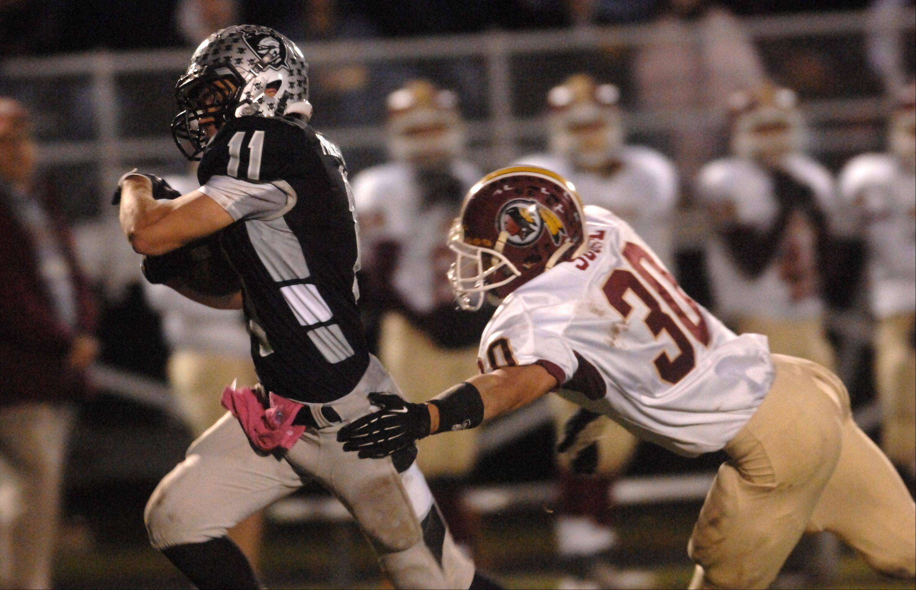 Kaneland's Zack Martinelli escapes the grasp of Morris' Reese Sobol en route to a 89-yard touchdown .