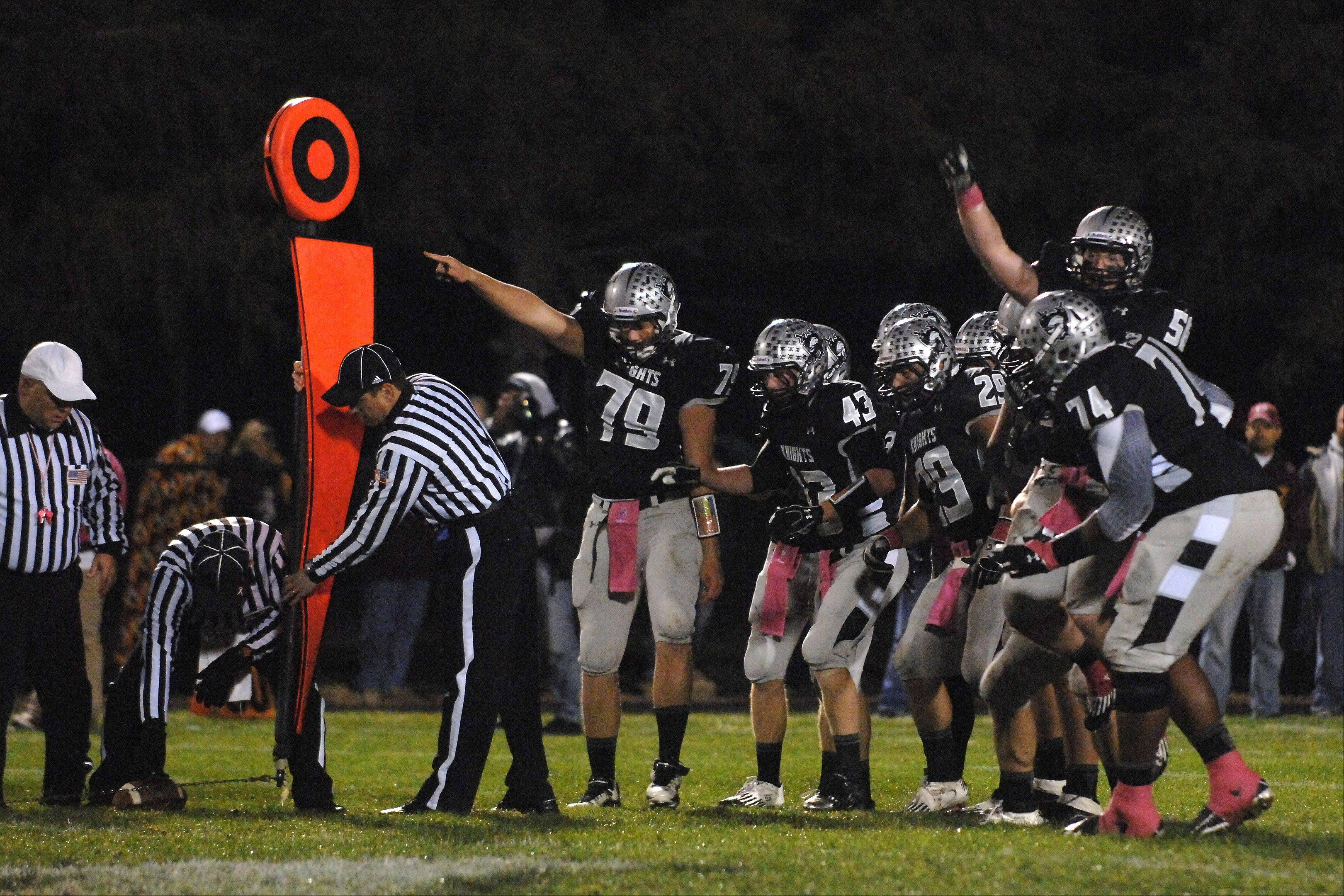 The Kaneland defense watches the chains to see they stopped Morris on a fourth down during the first quarter.