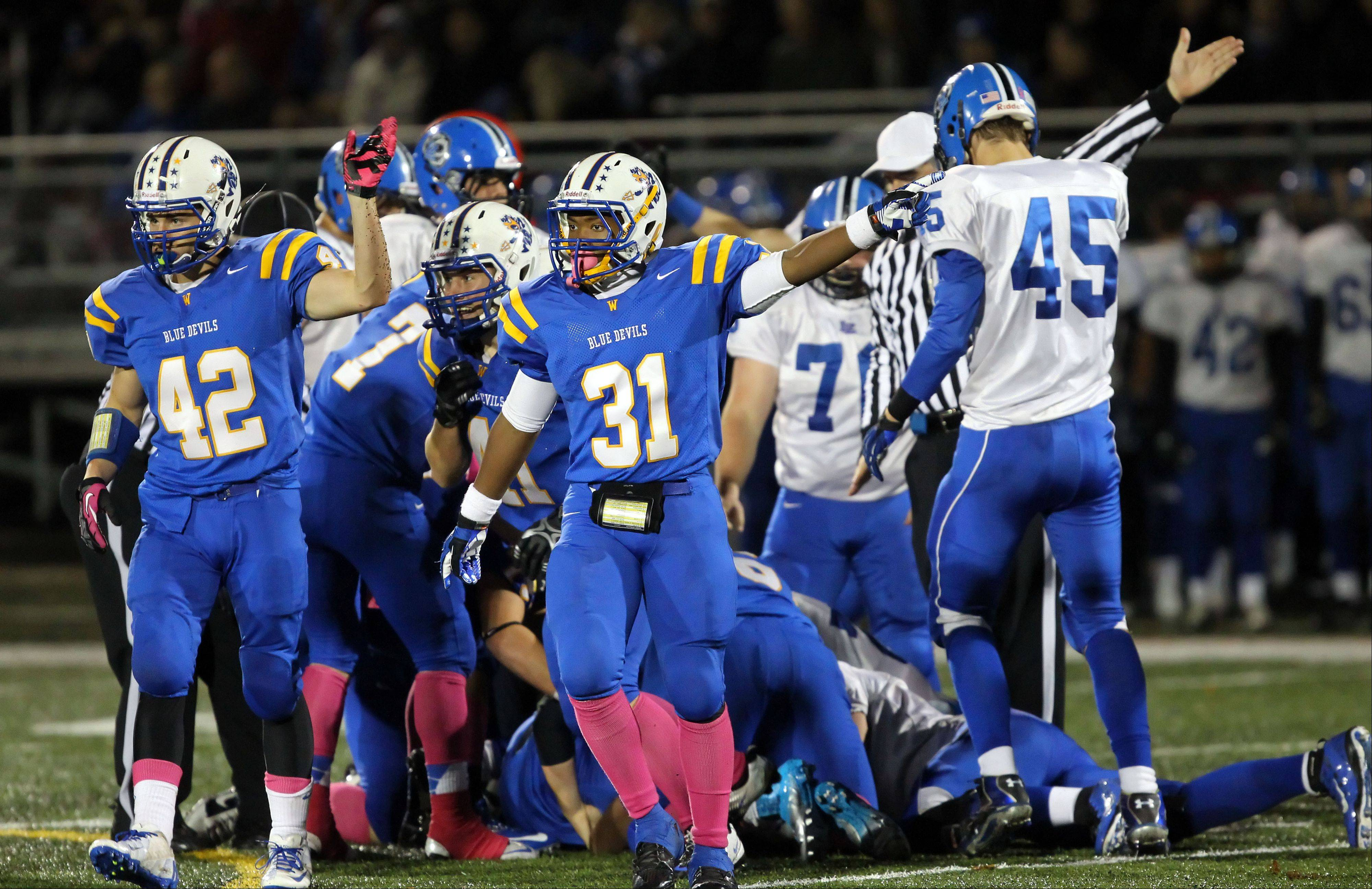 Members of the Warren defense signals after recovering a Lake Zurich fumble.