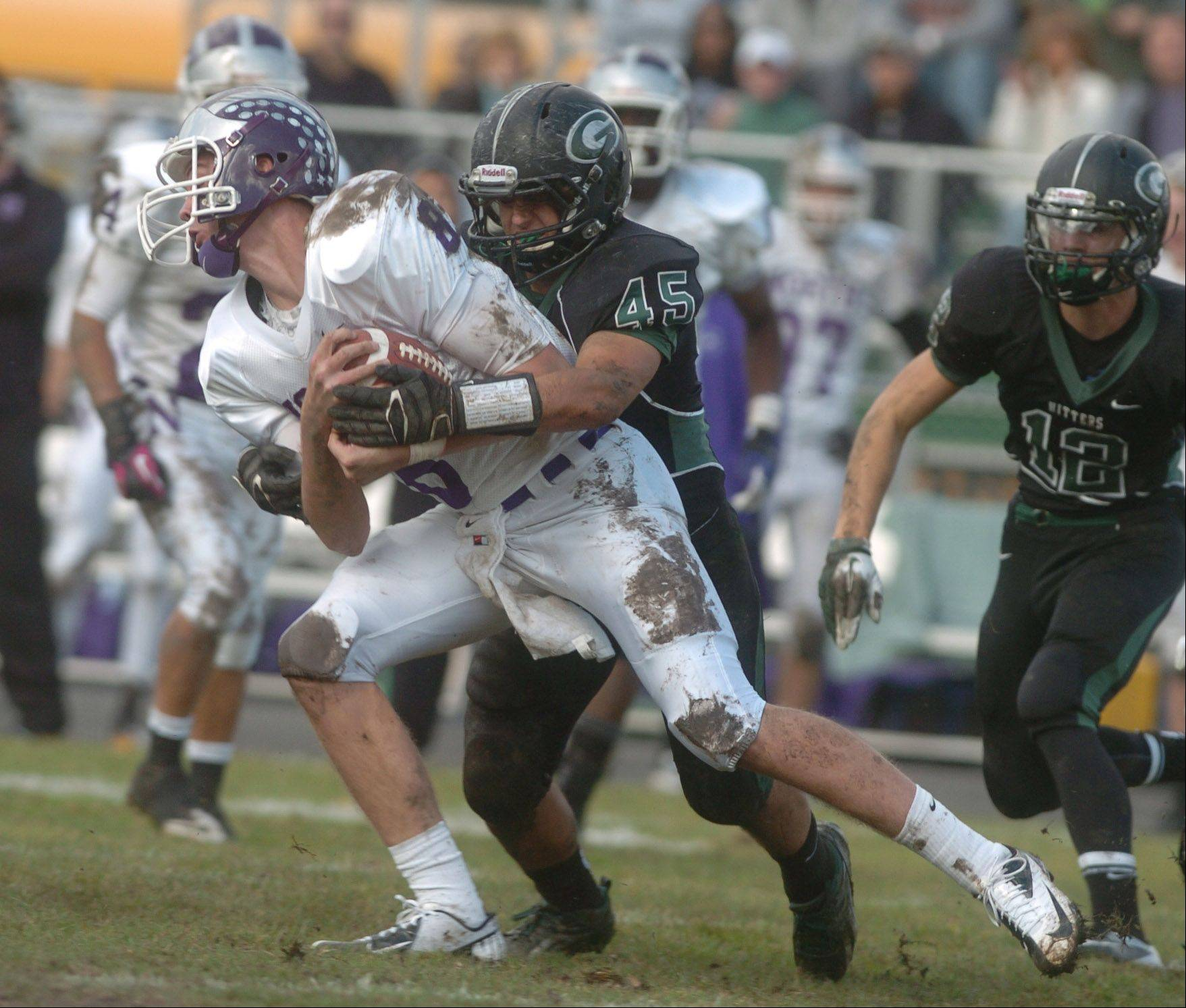 David Edwards of Downers Grove is pulled down by Jordan Hassan of Glenbard during the Downers Grove North at Glenbard West football game Saturday.